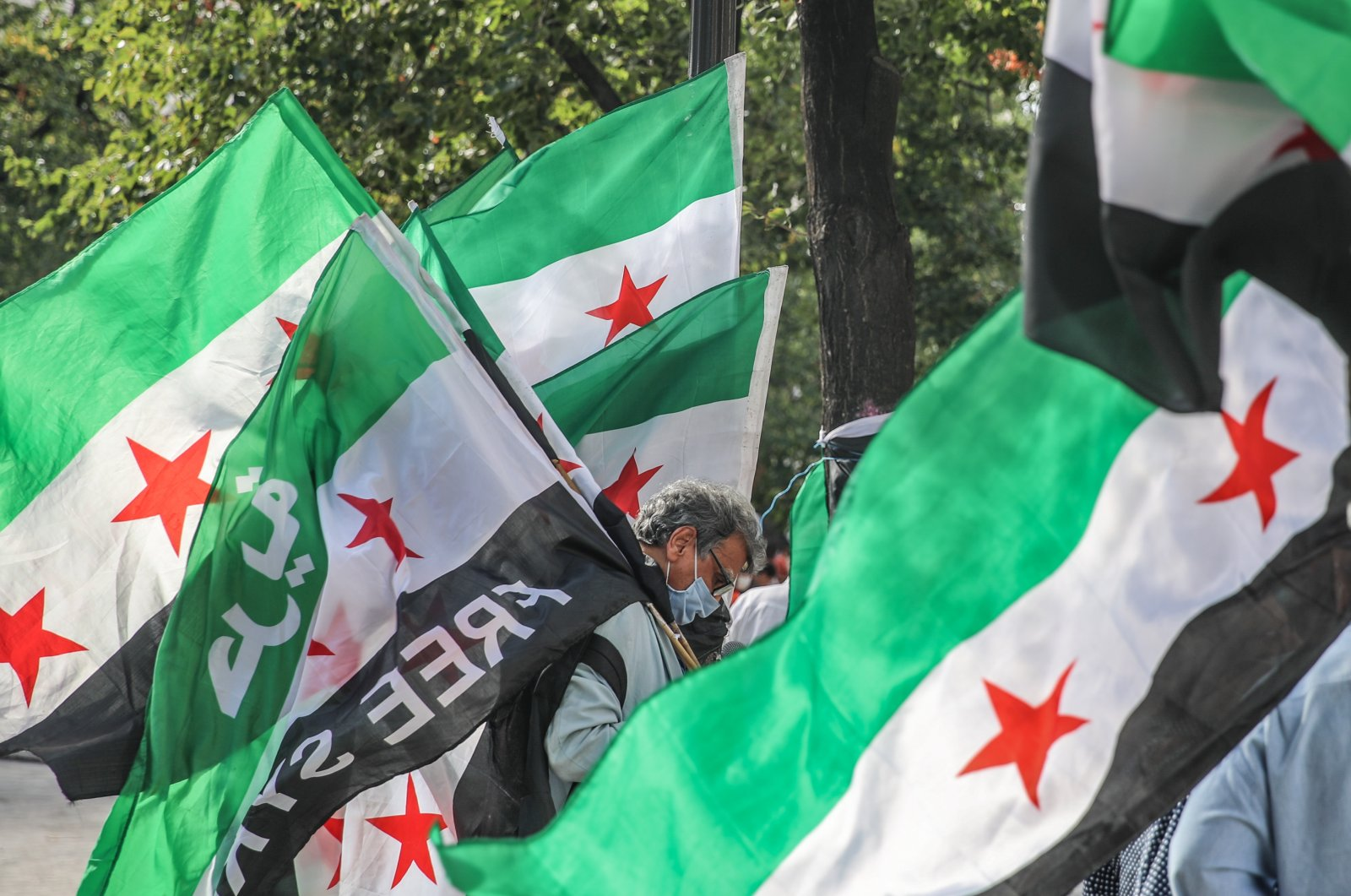 A Syrian activist carries the Syrian Revolution flag during a rally for the anniversary of 2013 Chemical Attack on Ghota, at Fontaine des Innocents in theLes Hallesdistrict in the1st arrondissementofParis,France. 21 August 2020. (EPA Photo)