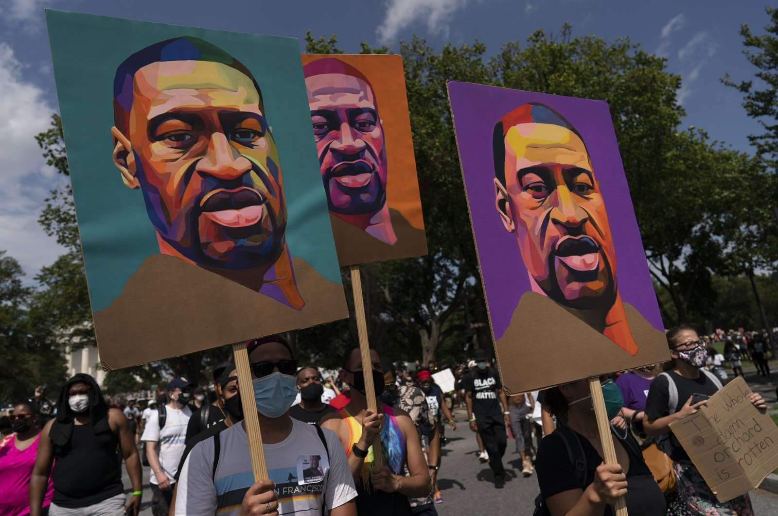 People carry posters of George Floyd as they march from the Lincoln Memorial to the Martin Luther King Jr. Memorial during the March on Washington, Friday Aug. 28, 2020, in Washington. (AP Photo)