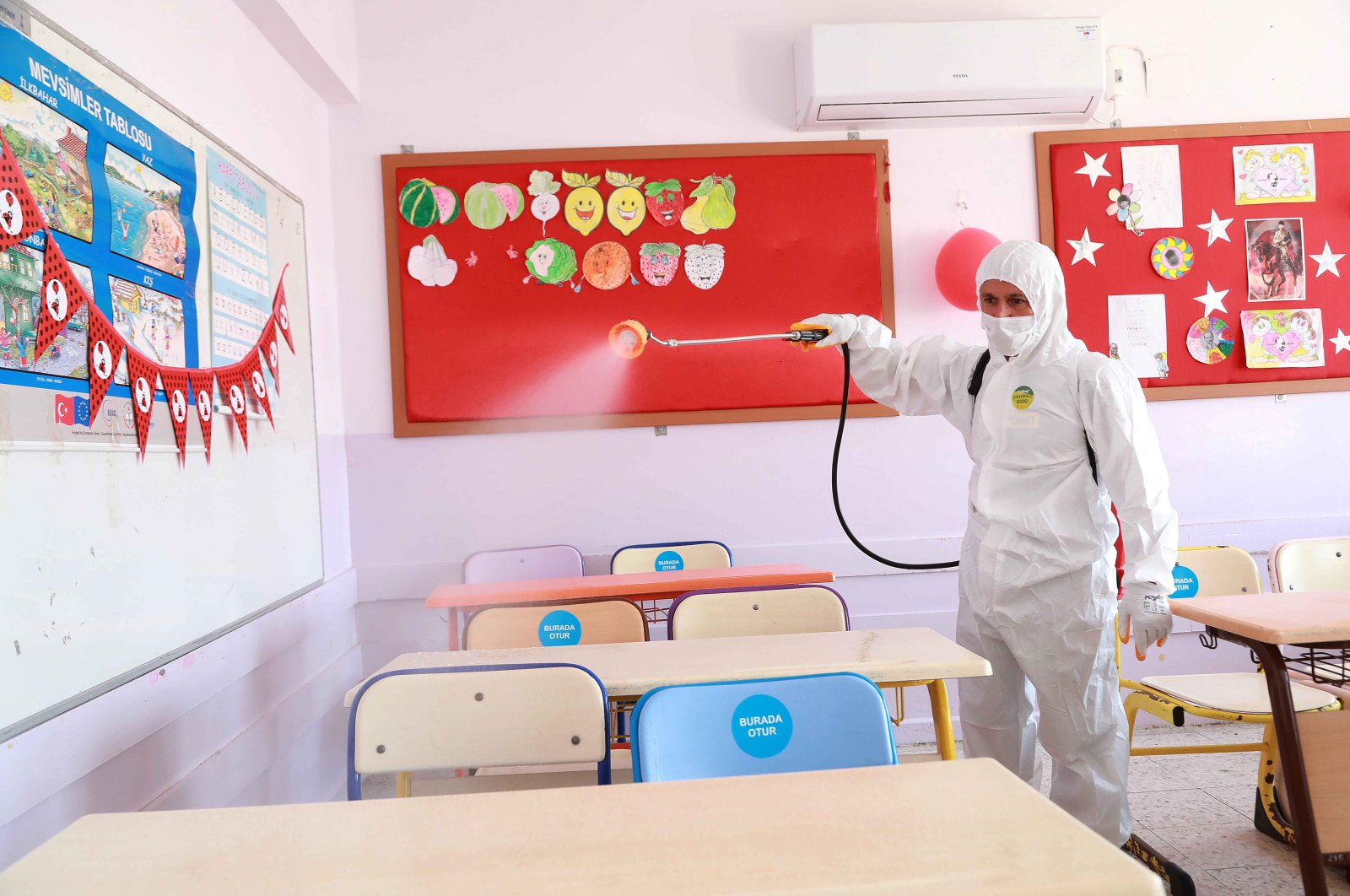 A worker disinfects a classroom at a school in the Bayraklı district, in İzmır, Turkey, Sept. 20, 2020. (IHA Photo)