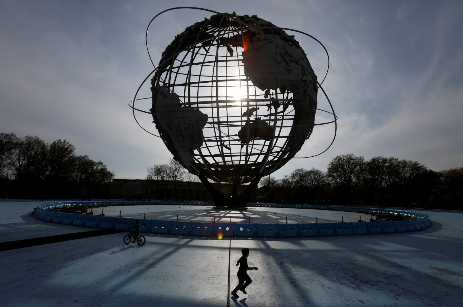 "A child plays under ""The Unisphere"" in Flushing Meadows-Corona Park during the outbreak of the coronavirus, in the Queens borough of New York City, April 25, 2020. (Reuters Photo)"
