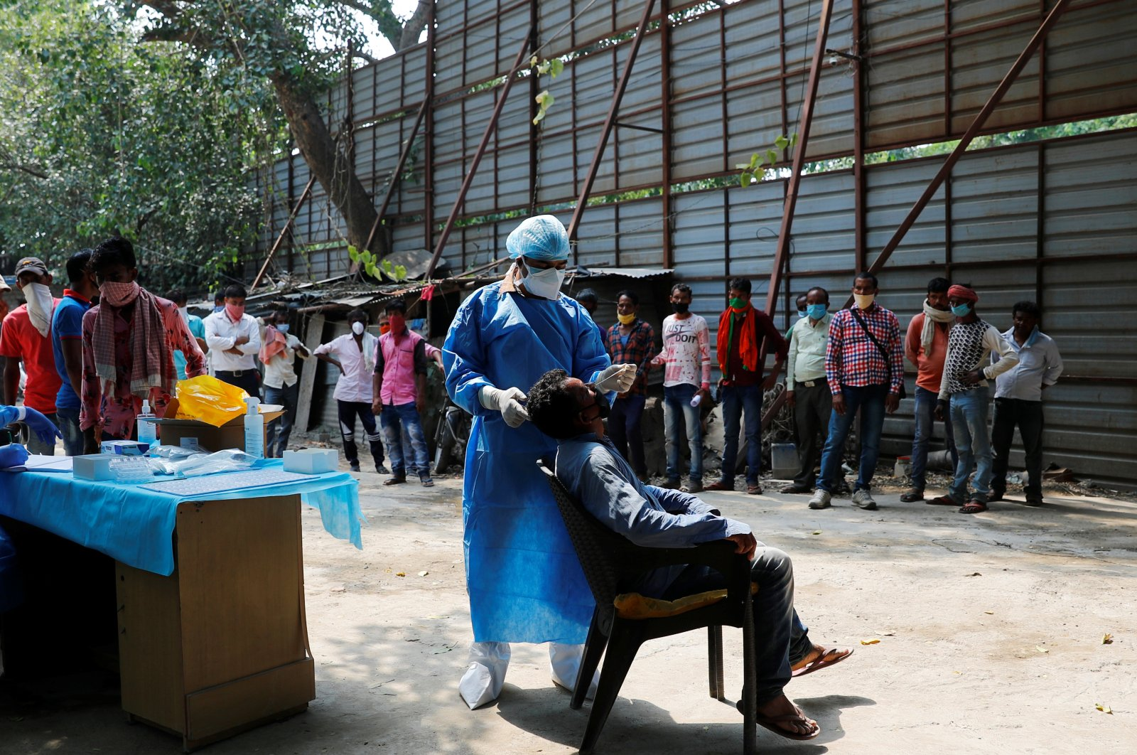 A health care worker wearing personal protective equipment (PPE) takes a swab from a migrant laborer for a rapid antigen test at the construction site for a residential complex amid a coronavirus outbreak in New Delhi, India, Sept. 19, 2020. (Reuters Photo)