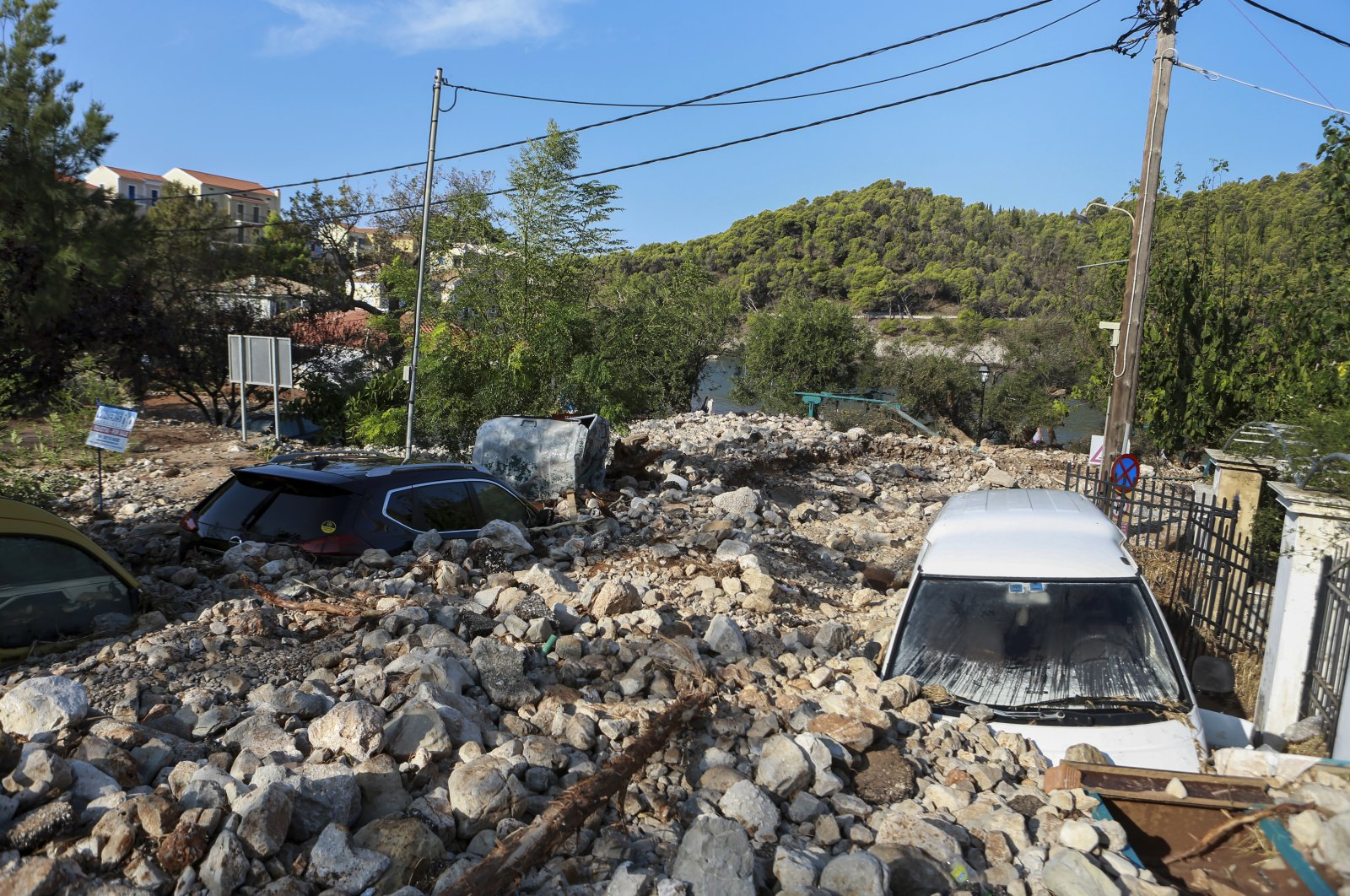 Vehicles are covered with rocks following a storm in the village of Assos, on the Ionian island of Kefalonia, western Greece, Sept. 20, 2020. (AP Photo)
