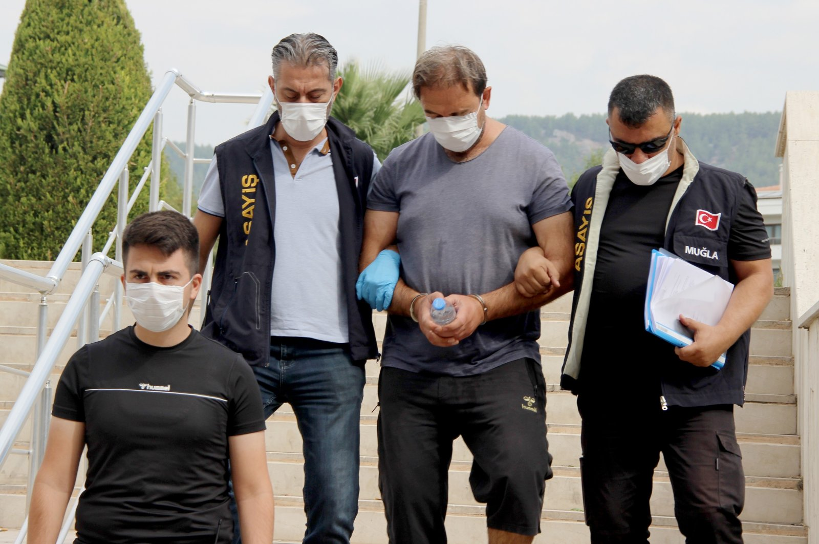 Police officers detainTayfun Demir, (C)in Muğla, Turkey, Sept. 20, 2020. (IHA Photo)