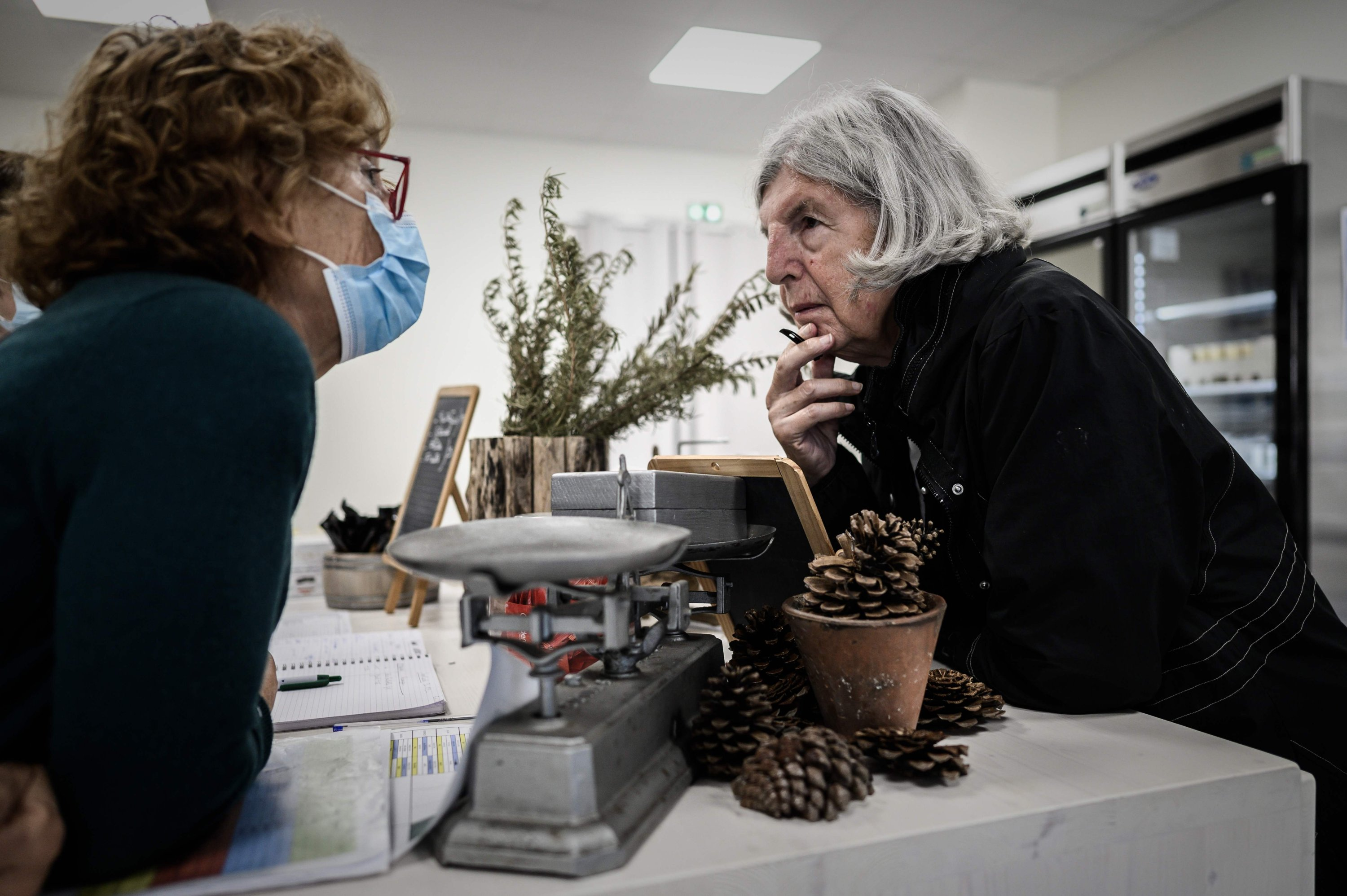 An Alzheimer's patient (R) chats with a staff member at the grocery store of the village Landais Alzheimer site for Alzheimer's patients in Dax, southwestern France, Sept. 9, 2020. (AFP Photo)