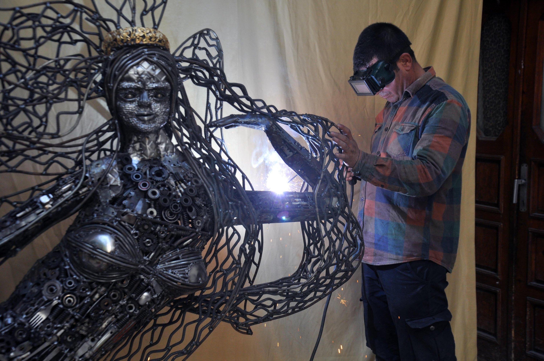 Scrap artist Mervan Altınorak works on his mermaid sculpture in the Reyhanlı district of Hatay, southern Turkey, Sept. 21, 2020. (DHA Photo)