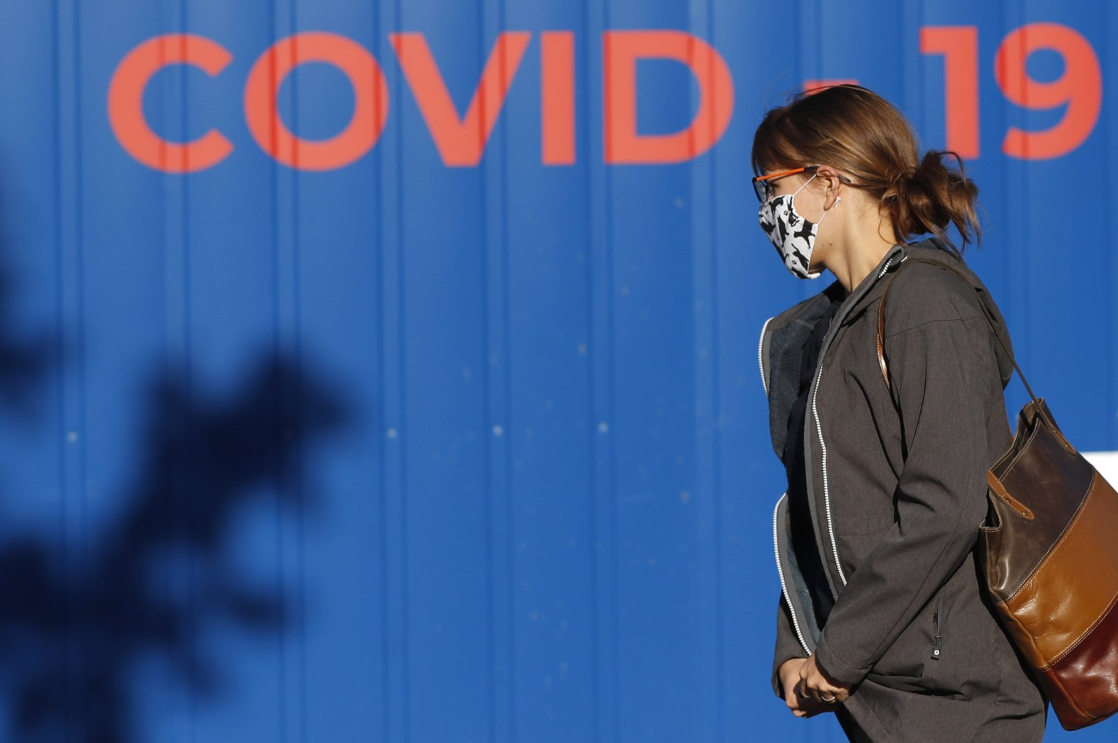 A woman wearing a face mask walks to get tested for COVID-19 at a sampling station in Prague, Czech Republic, Sept. 18, 2020. (AP Photo)