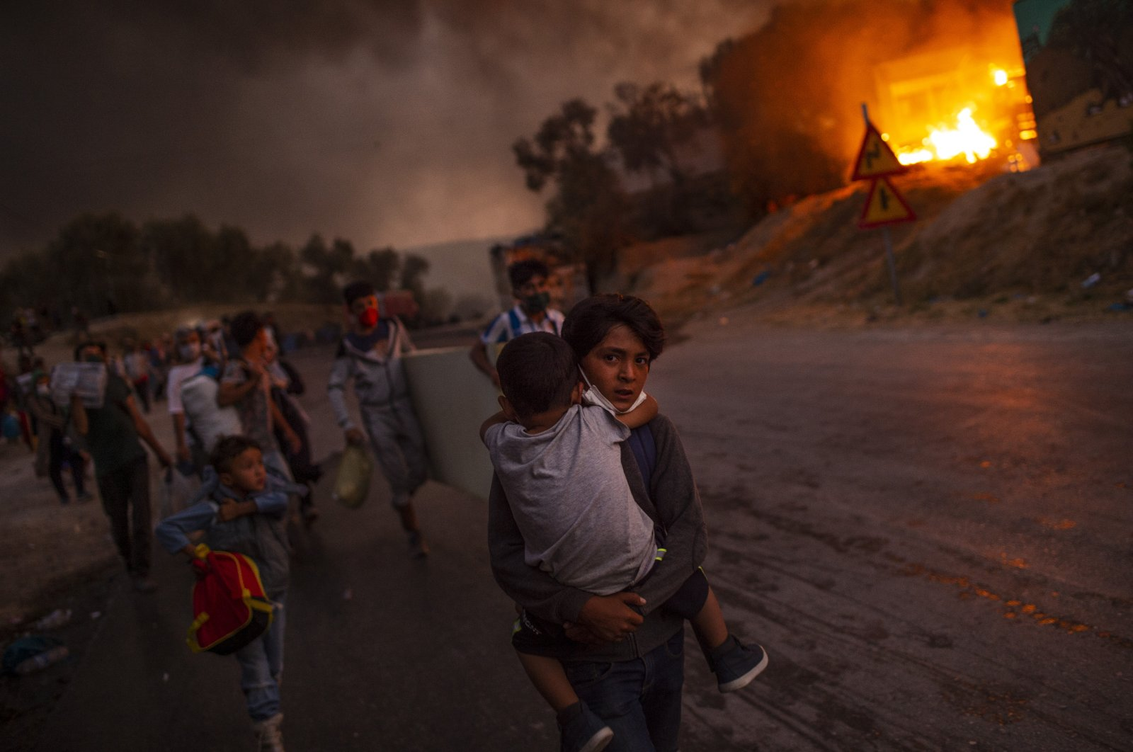 A boy carries a child in his arms as migrants flee the Moria camp after a fire broke out, on the island of Lesbos, Greece, Sept. 9, 2020. (AFP Photo)