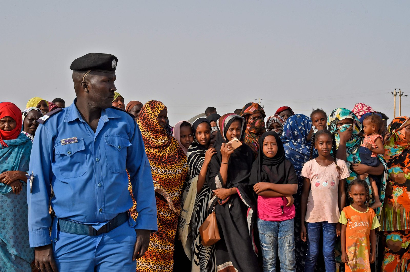 A policeman looks on while standing before displaced people at a shelter camp in the village of Tamaniyet, north of Sudan's capital Khartoum, Sept. 14, 2020. (AFP Photo)