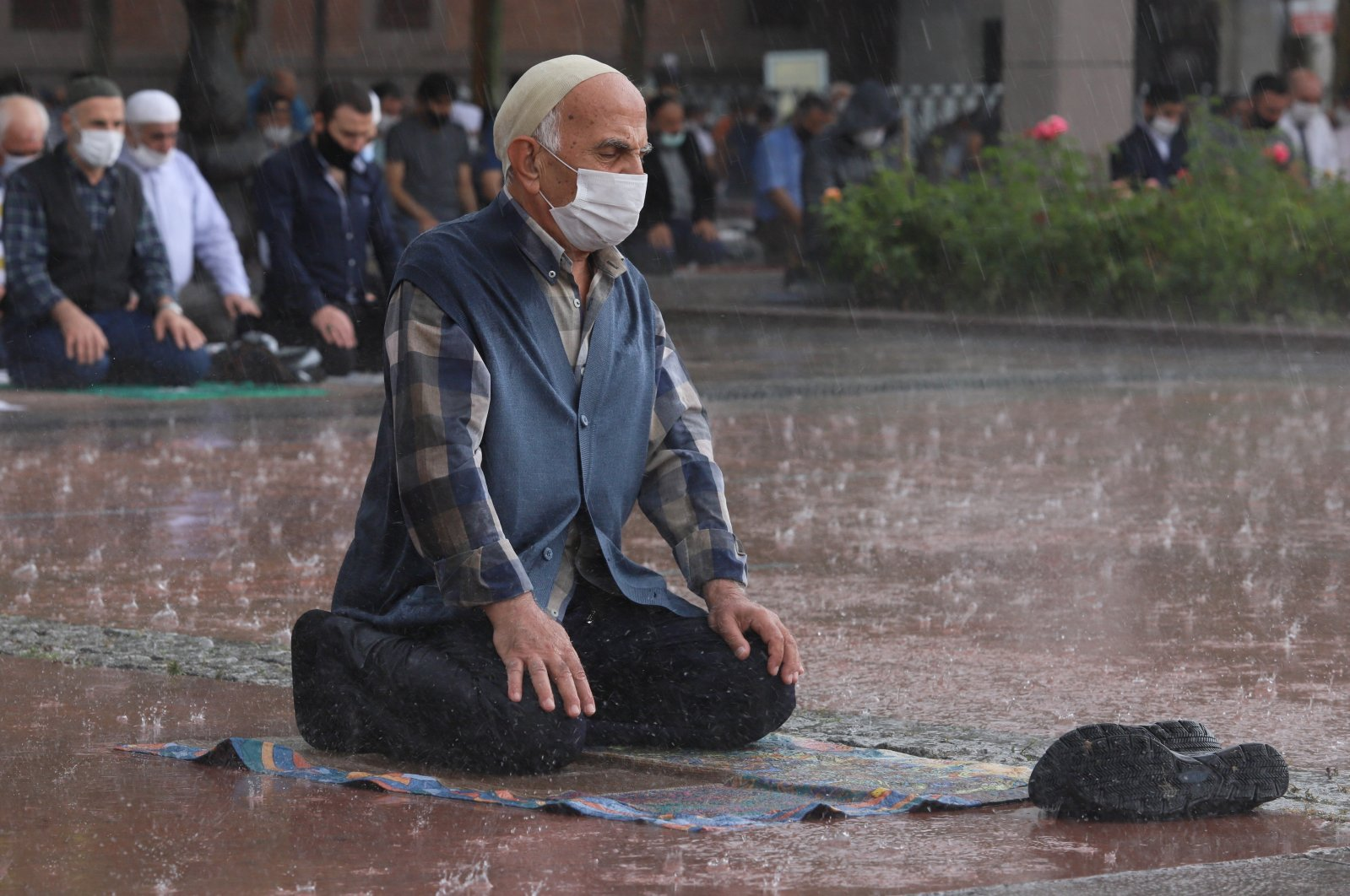 A man prays as it rains in the courtyard of a mosque which was opened months after COVID-19-induced lockdowns in Ankara, June 19, 2020. (IHA Photo)