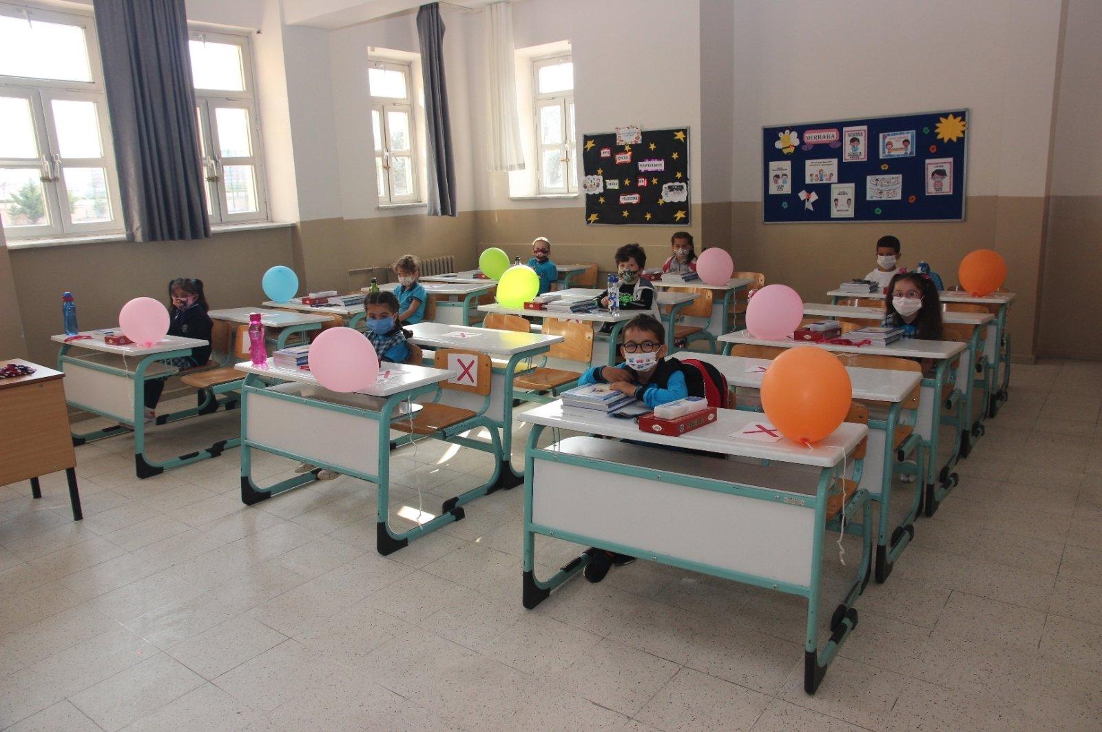 Children wearing protective masks sit inside a classroom, in Bursa, northwestern Turkey, Sept. 21, 2020. (DHA Photo)