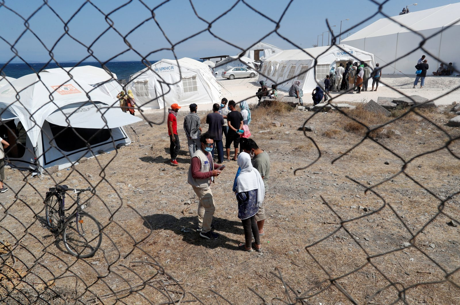 Aid workers and residents are seen at the new temporary camp for migrants and refugees, on the island of Lesbos, Sept. 21, 2020. (REUTERS Photo)