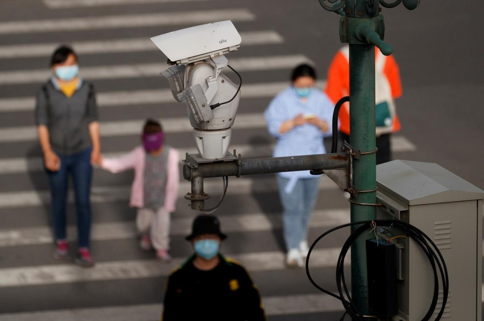 A CCTV security surveillance camera overlooks a street as people walk following the spread of COVID-19 in Beijing, China, May 11, 2020. (Reuters Photo)