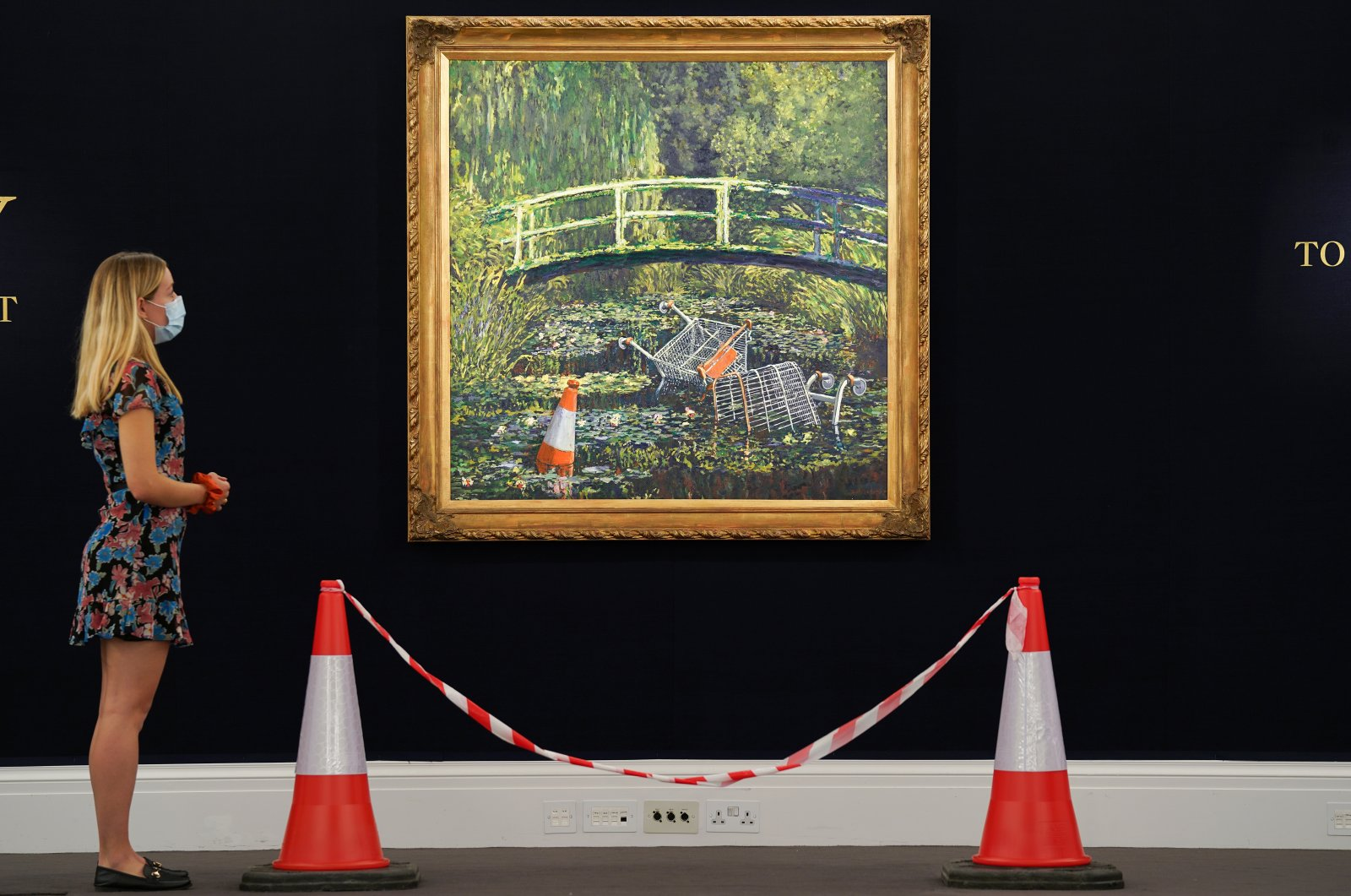 """A visitor stands in front of a painting by the artist Banksy, titled """"Show me the Monet,"""" at Sotheby's in London, Britain, Sept. 18, 2020. (Sotheby's handout via Reuters)"""