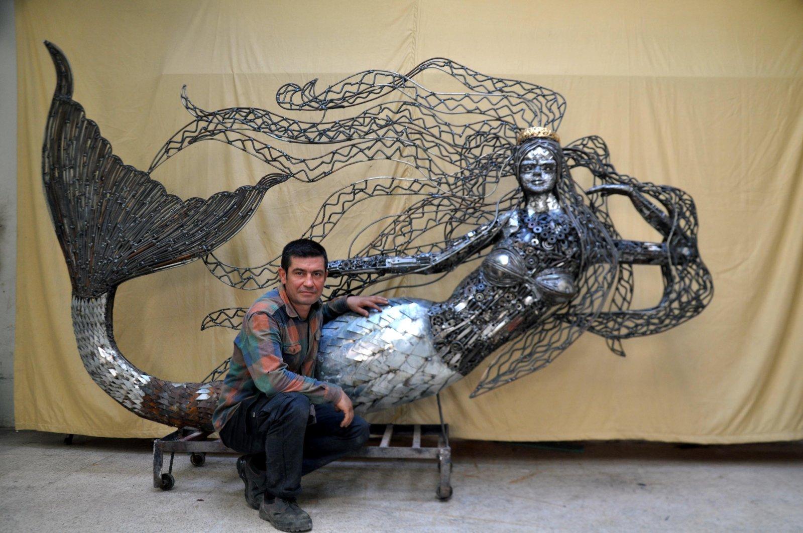 Scrap artist Mervan Altınorak stands beside his sculpture of a mermaid in the Reyhanlı district of Hatay, southern Turkey, Sept. 21, 2020. (DHA Photo)