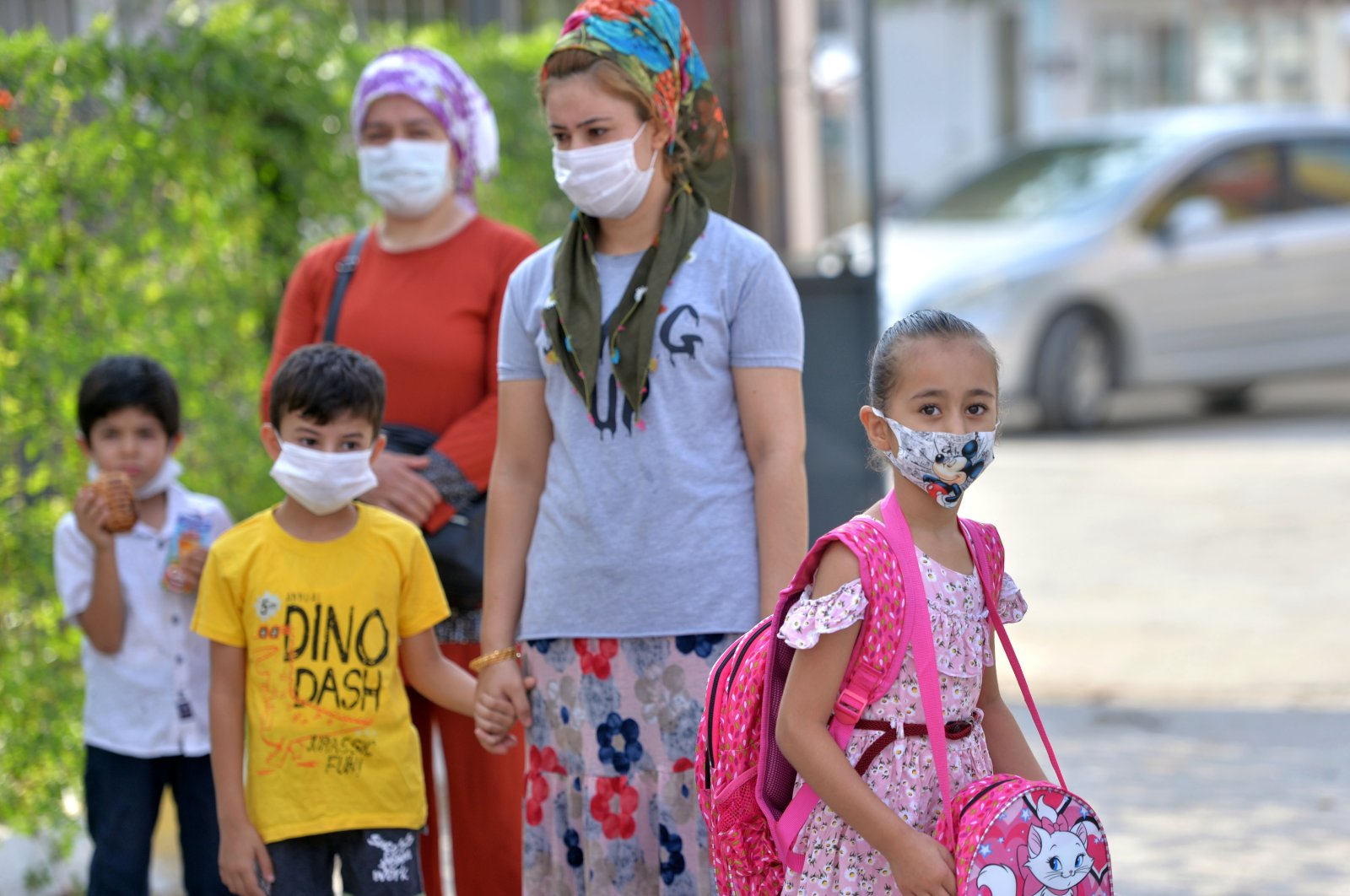 Children wearing protective face masks walk with their mothers on the first day schools opened to kindergarten and first grade students, in Mersin, southern Turkey, Sept. 21, 2020. (AA Photo)