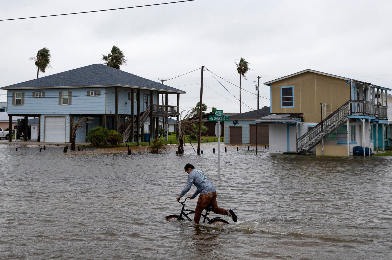 A boy rides his bike down a flooded South Magnolia Street in Rockport, Texas, U.S., as Tropical Storm Beta approaches, Sept. 21, 2020. (Reuters Photo)