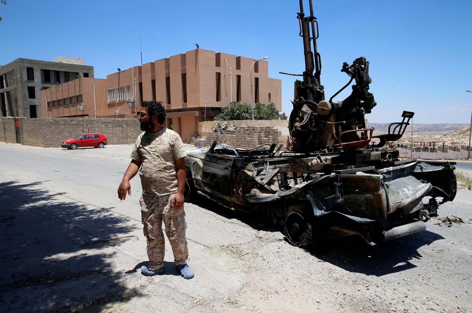 A member of forces allied to Libya's internationally recognized government stands near a destroyed military vehicle that belonged to putschist Gen. Khalifa Haftar, in Gharyan, south of Tripoli, Libya, June 27, 2019. (Reuters Photo)