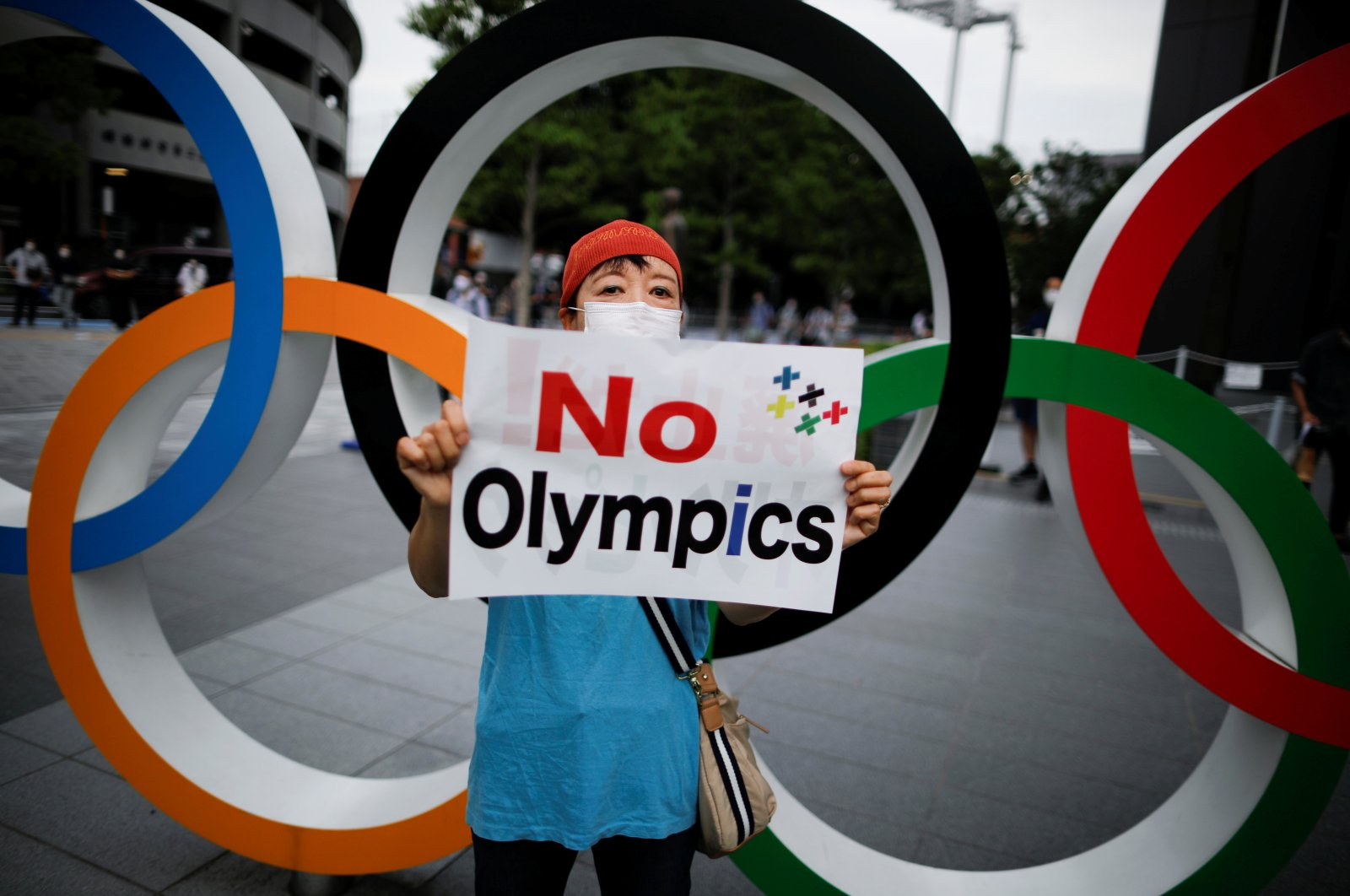 A demonstrator wearing a face mask holds a sign to protest against the Tokyo 2020 Olympic Games, in Tokyo, Japan on July 24, 2020. (Reuters Photo)