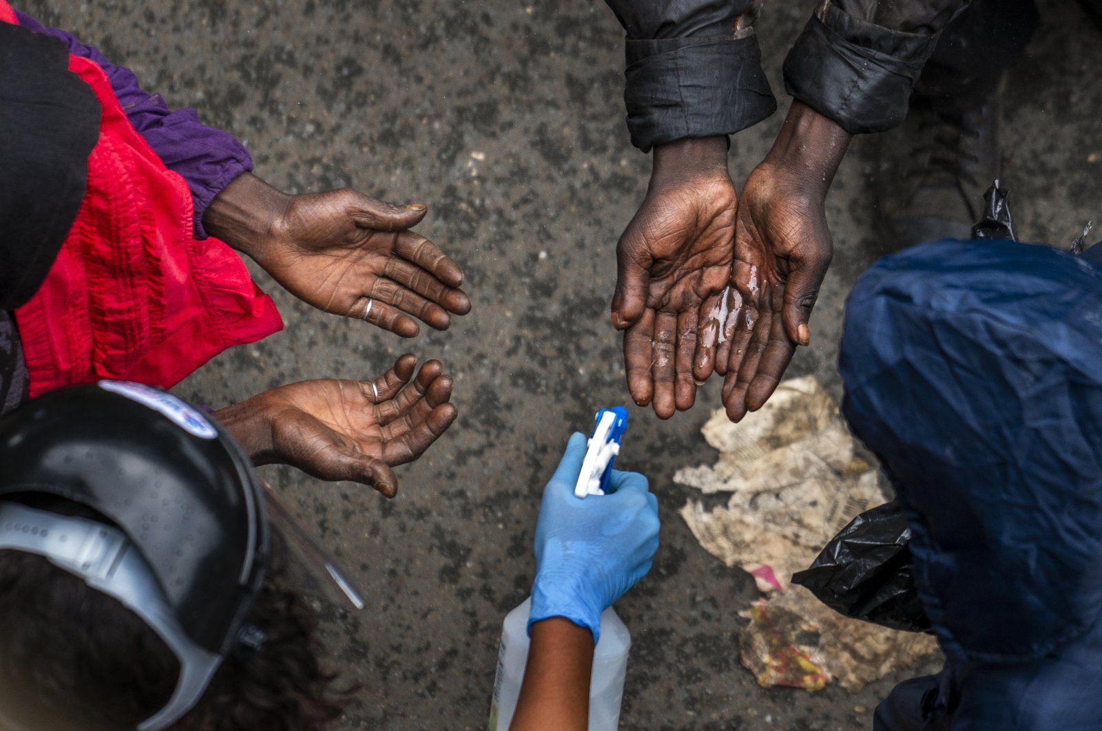 Homeless people waiting to receive food baskets from private donors get their hands sanitized in downtown Johannesburg, South Africa, April 13, 2020. (AP Photo)