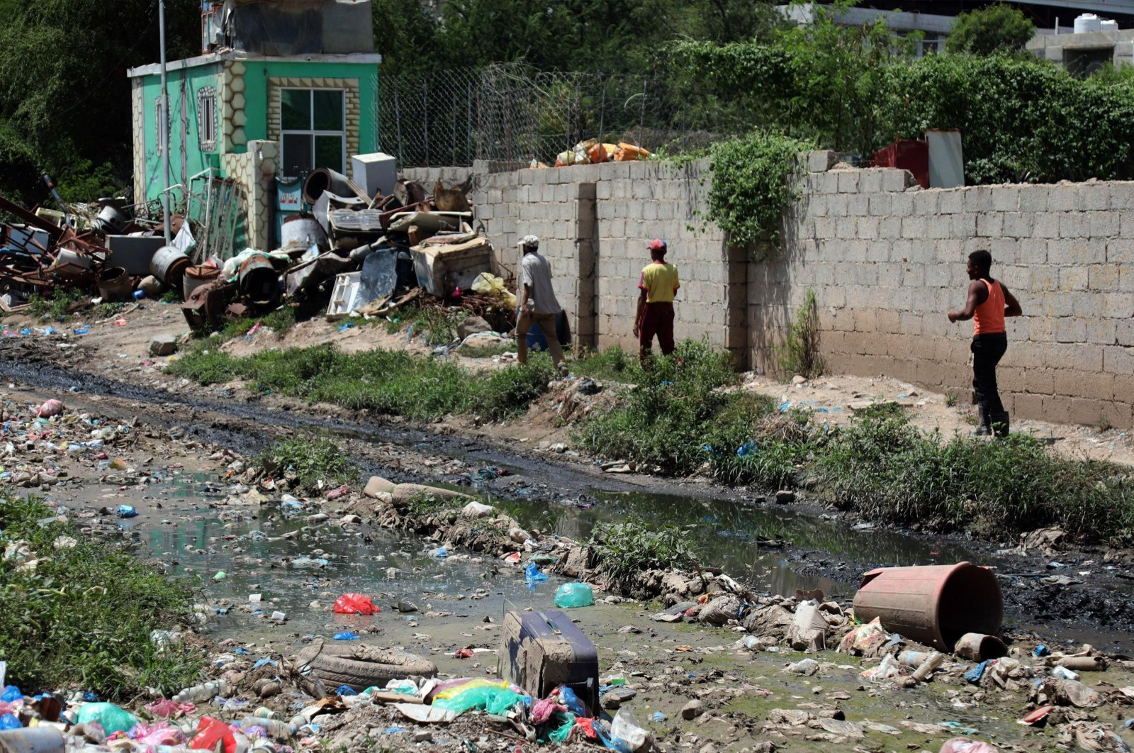 People walk along open sewers and scattered rubbish in Yemen's third city of Taiz, Sept. 19, 2020. (AFP Photo)
