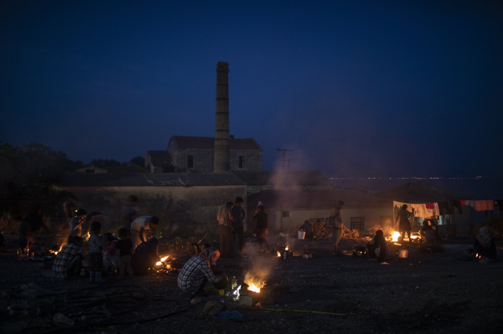 Refugees and migrants from the destroyed Moria camp cook over makeshift fires, on the island of Lesbos, Greece, Sept. 17, 2020. (AP Photo)
