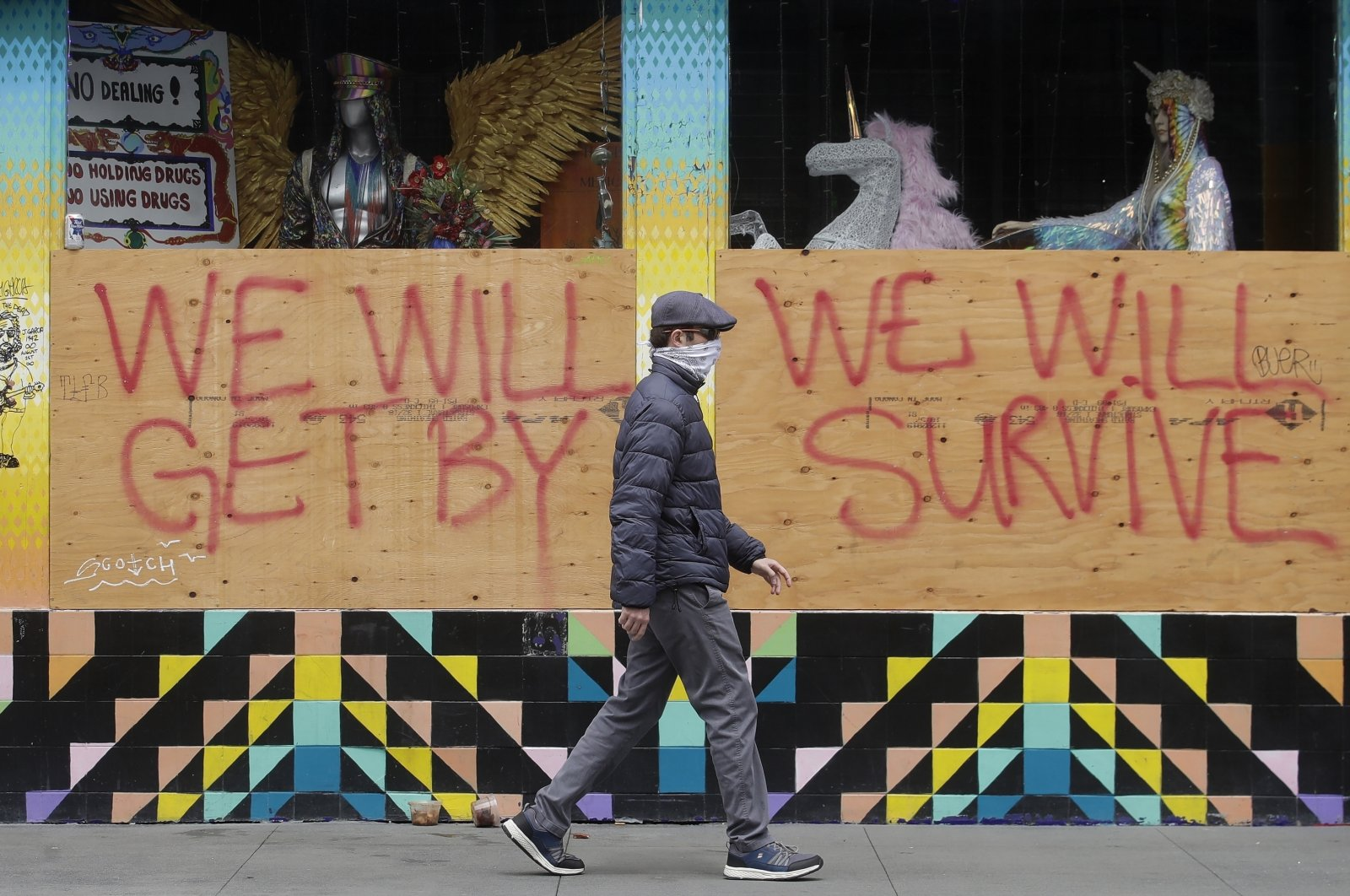 A man wears a face mask while walking past signs posted over windows of a store in the Haight-Ashbury district, San Francisco, California, U.S., April 18, 2020. (AP Photo)