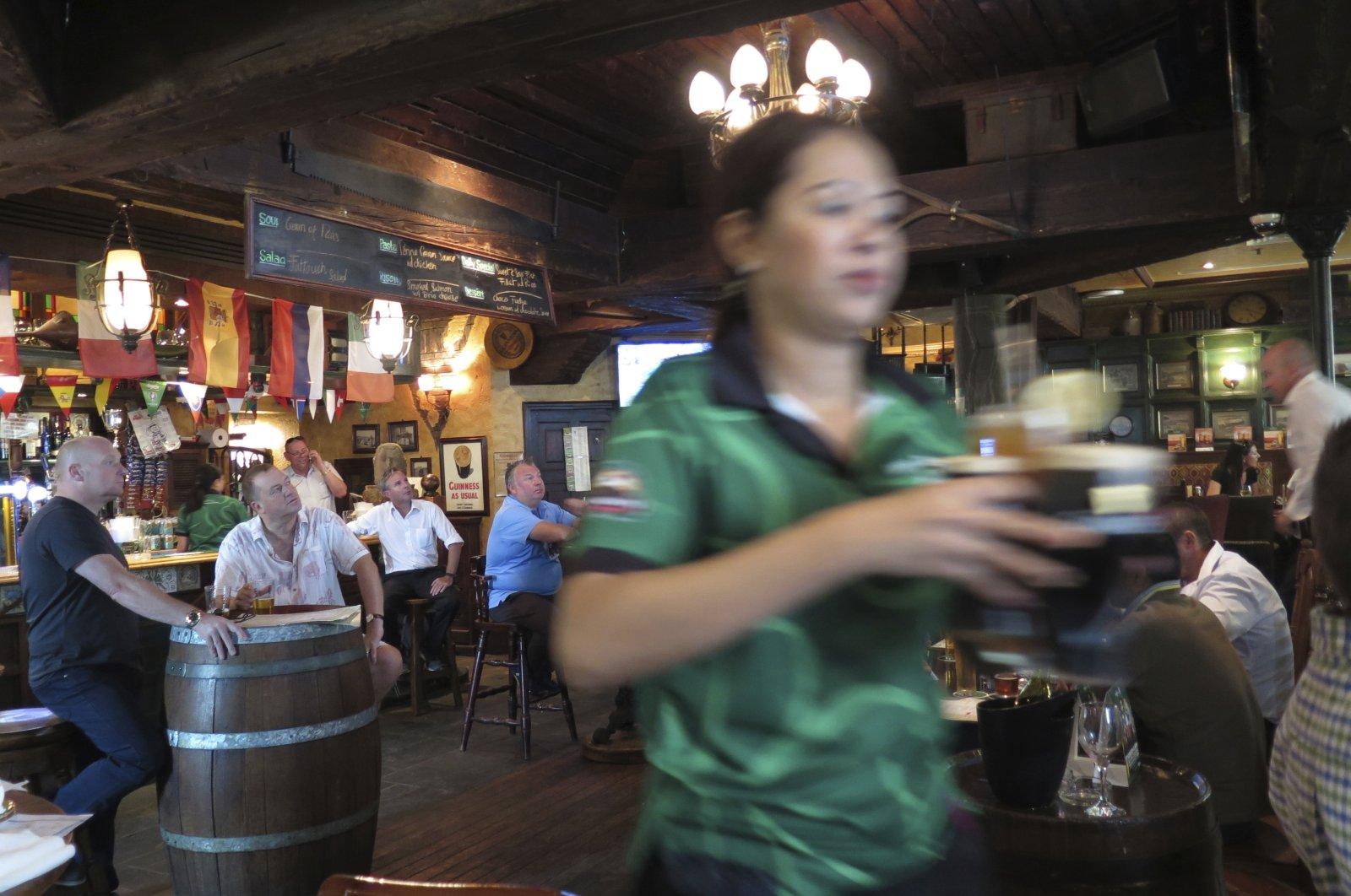 A waitress serves customers beer at a restaurant in Dubai, United Arab Emirates, June 22, 2016 . (AP Photo)