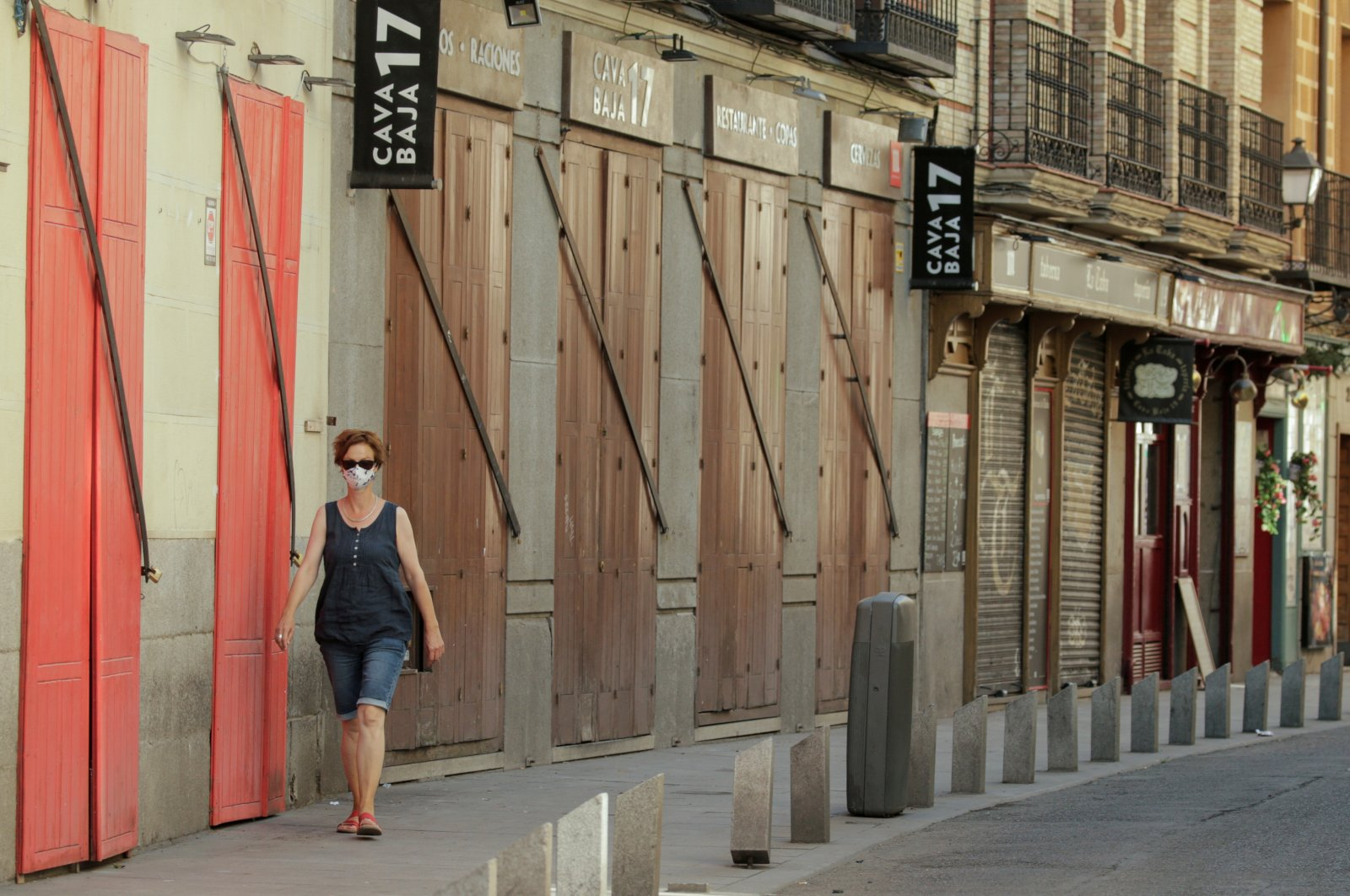 A woman wearing a protective mask walks past closed restaurants, amid the coronavirus disease (COVID-19) outbreak, in Madrid, July 31, 2020. (Reuters Photo)