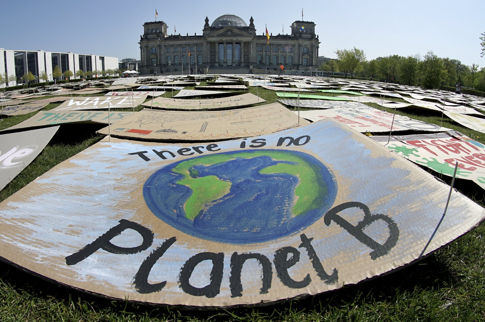 """In this April 24, 2020, file photo, activists place thousands of protest placards in front of the Reichstag building, home of the german federal parliament, Bundestag, during a protest rally of the """"Fridays for Future"""" movement in Berlin, Germany.  (AP Photo)"""