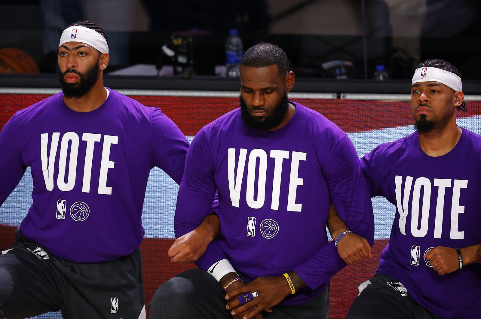 Los Angeles Lakers' Anthony Davis (L) LeBron James (C) and Quinn Cook kneel the national anthem during the first half of an NBA conference final playoff basketball game against the Denver Nuggets, in Lake Buena Vista, Florida, U.S., Sept. 22, 2020. (AFP Photo)