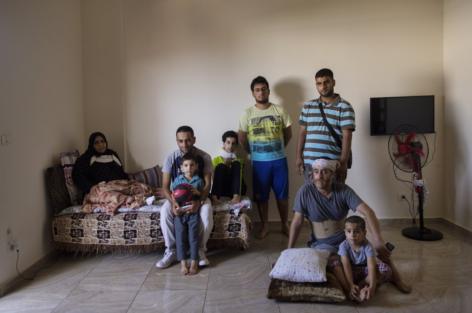 The family of Ali Kinno poses for a photograph, (from L to R) Fatmeh Kinno, 45, Mahmoud, 25, Hoda, 11, Qoteiba, 17, Mustafa, 28, Ali, 45 and Ahmad, 6, during an interview at a temporary apartment in the coastal town of Jiyeh, south of Beirut, Lebanon, Sept. 15, 2020. (AP Photo)