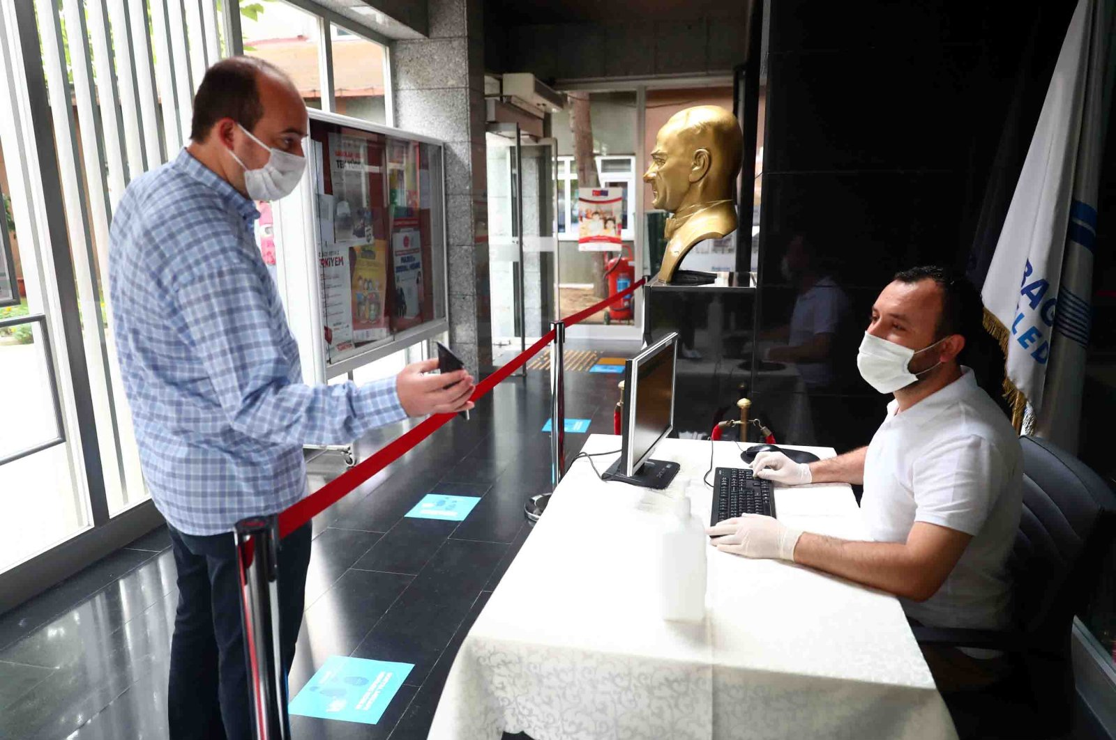 A man shows his HES code via phone to a receptionist as he enters a municipality building in Bağcılar district, Istanbul, Turkey, Sept. 23, 2020. (DHA Photo)