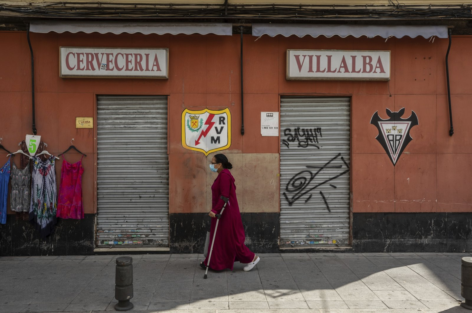 A woman wearing a face mask to prevent the spread of the coronavirus walks in the southern neighborhood of Vallecas, Madrid, Sept. 21, 2020. (AP Photo)