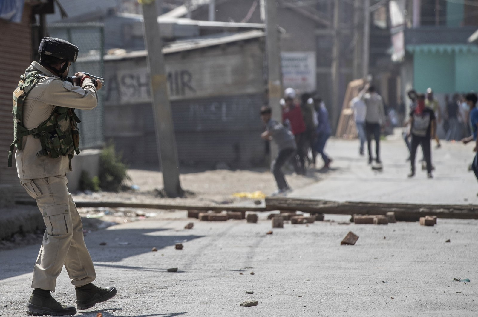 An Indian paramilitary soldier aims his pellet gun on Kashmiri protesters marching on the streets in solidarity with rebels engaged in a gunbattle with soldiers, in Srinagar, Indian controlled Kashmir, Sept. 17, 2020. (AP Photo)