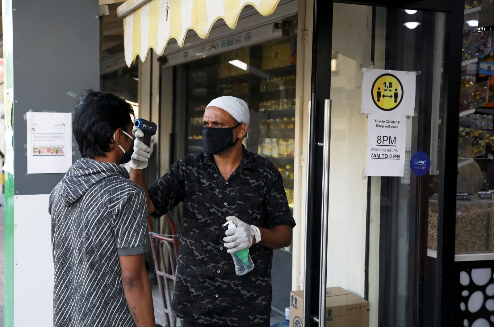 A man wearing a protective face mask has his temperature taken outside a corner store, following the outbreak of COVID-19 in the Al Quoz industrial district of Dubai, UAE, April 14, 2020. (Reuters Photo)
