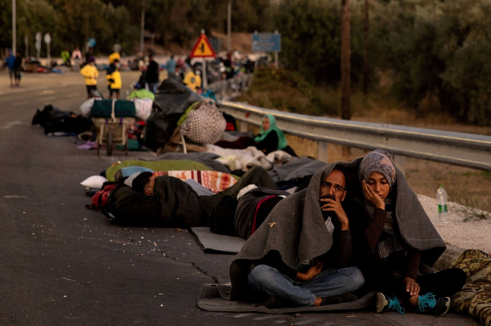 A couple sits covered with a blanket as refugees and migrants camp on a road following a fire at the Moria camp on the island of Lesbos, Sept. 10, 2020. (REUTERS Photo)