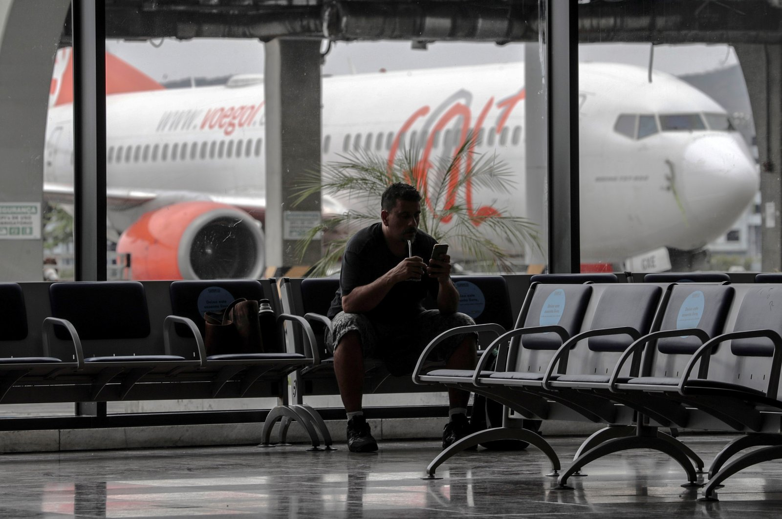 A man checks his phone in a waiting room at Santos Dumont airport, in Rio de Janeiro, Brazil, Aug. 20, 2020. (EPA Photo)