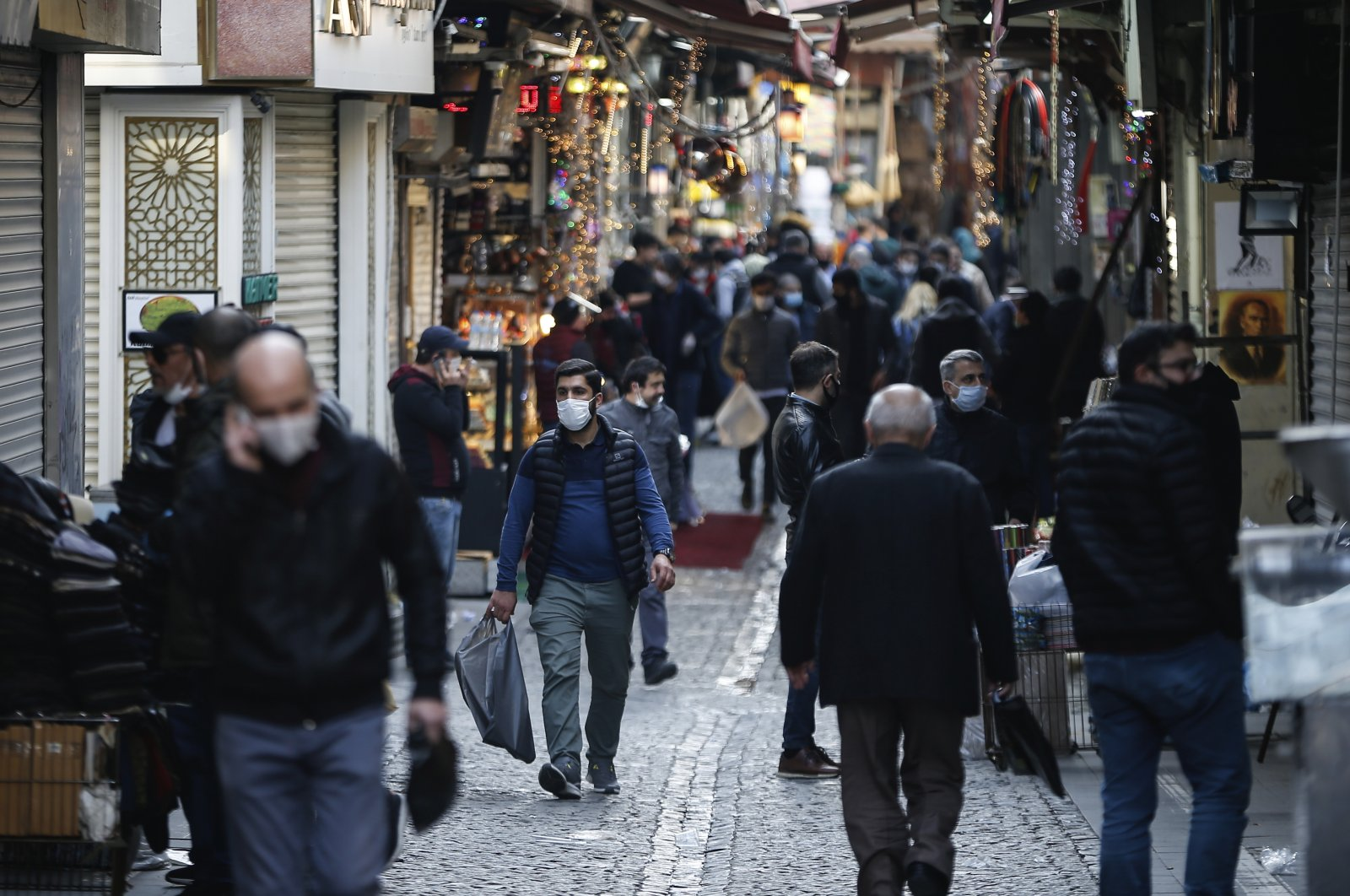 People, some wearing masks as a preventive measure against the spread of coronavirus, walk at Eminonu Bazaar in Istanbul, Friday, April 17, 2020. (AP Photo)