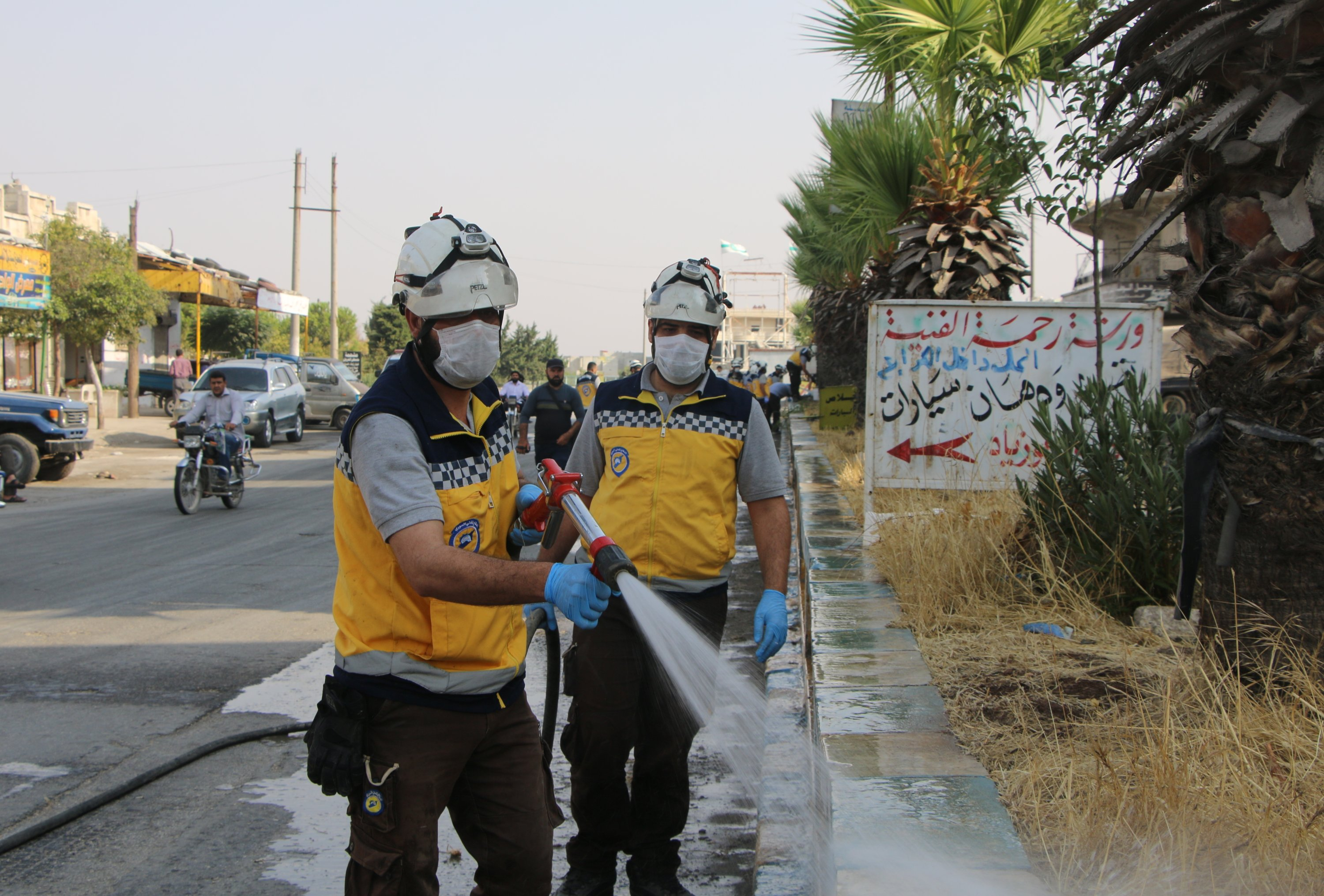 White Helmets volunteers wash town streets in an effort to recover from the damage left by Syrian regime attacks, Idlib, Syria, Sept. 24. 2020. (AA)