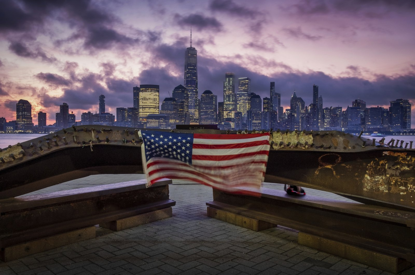 A U.S. flag hanging from a steel girder, damaged in the Sept. 11, 2001 attacks on the World Trade Center in New York City, blows in the breeze at a memorial as the sun rises behind the One World Trade Center building and the re-developed area where the Twin Towers of the World Trade Center once stood in New York City on the 18th anniversary of the attacks, Jersey City, New Jersey, Sept. 11, 2019. (AP Photo)