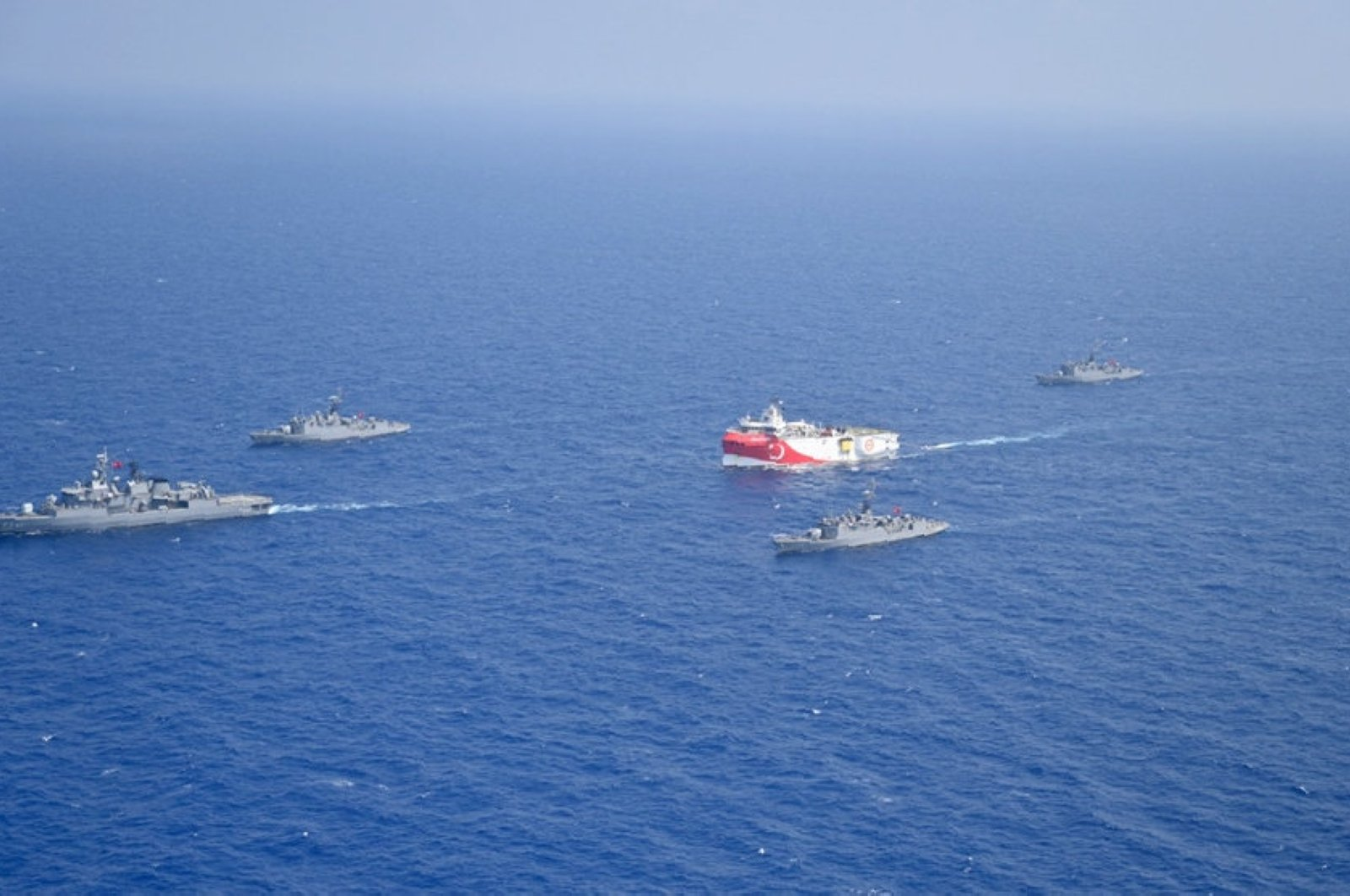 Turkey's research vessel Oruç Reis, in red and white, is surrounded by Turkish navy vessels as it heads to the west of southern Antalya province, Turkey, in the Mediterranean, Aug 10, 2020. (AP Photo)