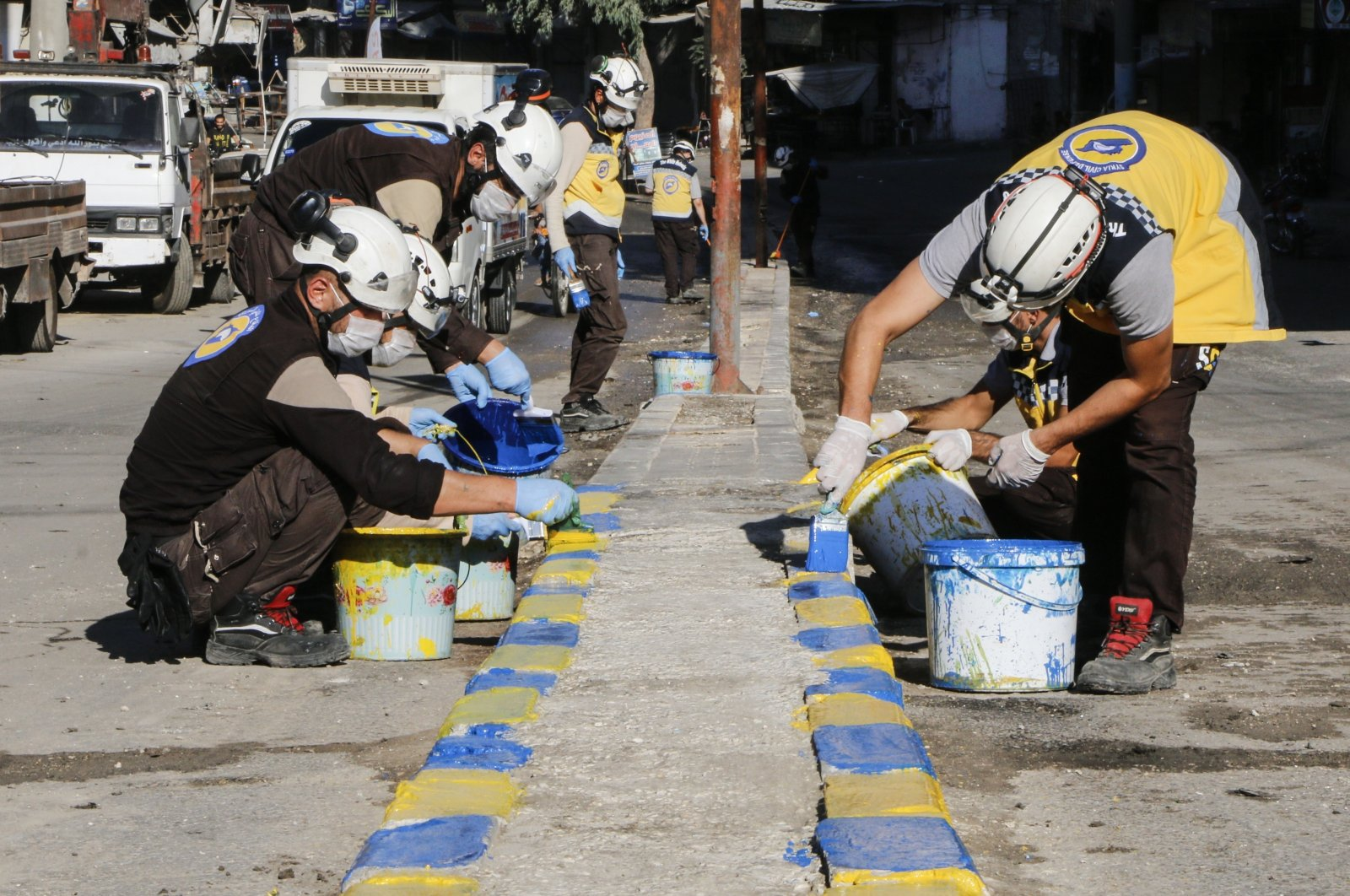 White Helmets volunteers paint flagstones in an effort to beautify streets damaged by Syrian regime attacks, Idlib, Syria, Sept. 24. 2020. (AA)