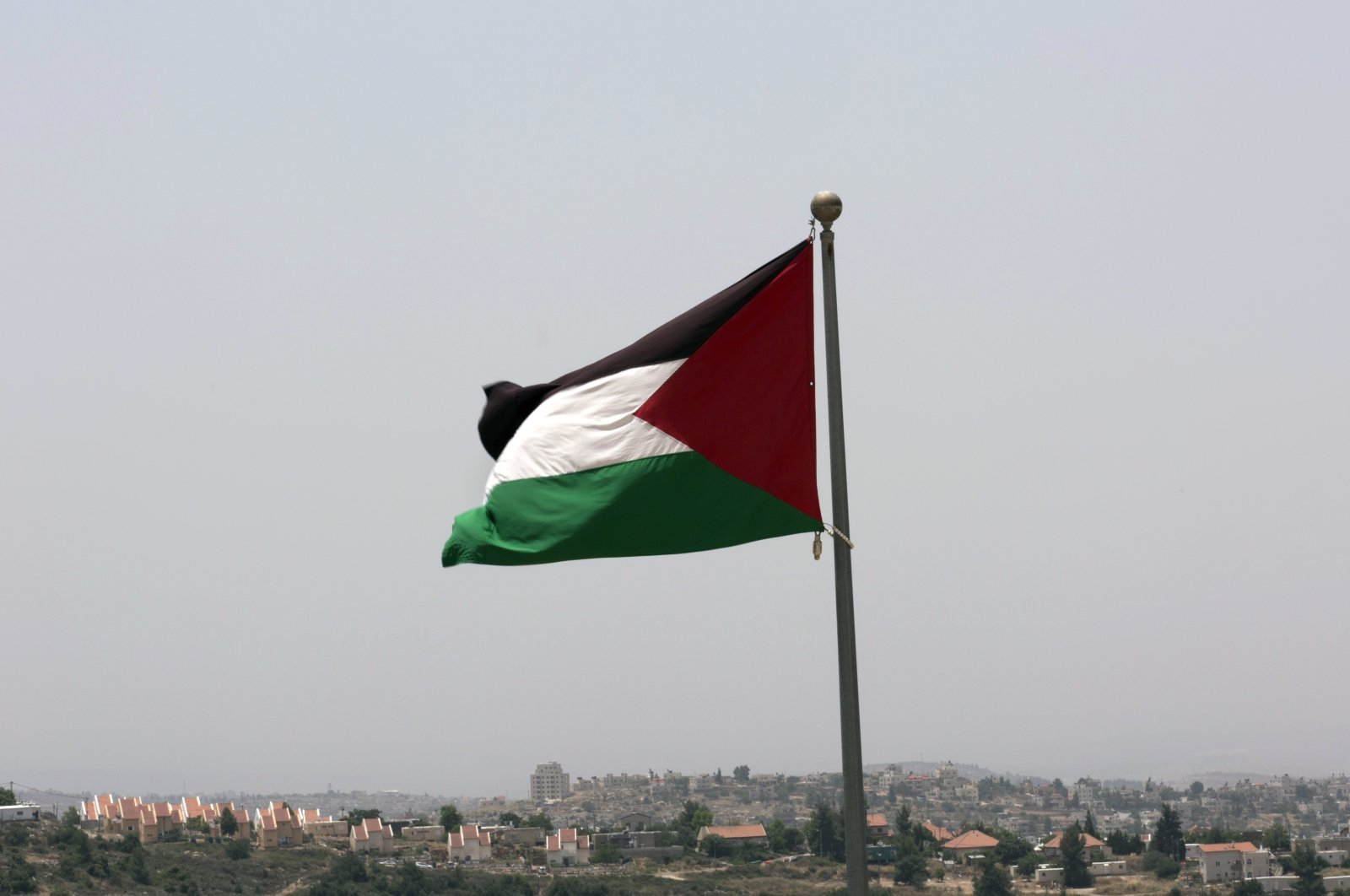 The Israeli settlement of Ateret is seen in the background as the Palestinian national flag flies from the highest point of the occupied West Bank city of Rawabi, north of Ramallah, Palestine, June 4, 2016. (AP Photo)