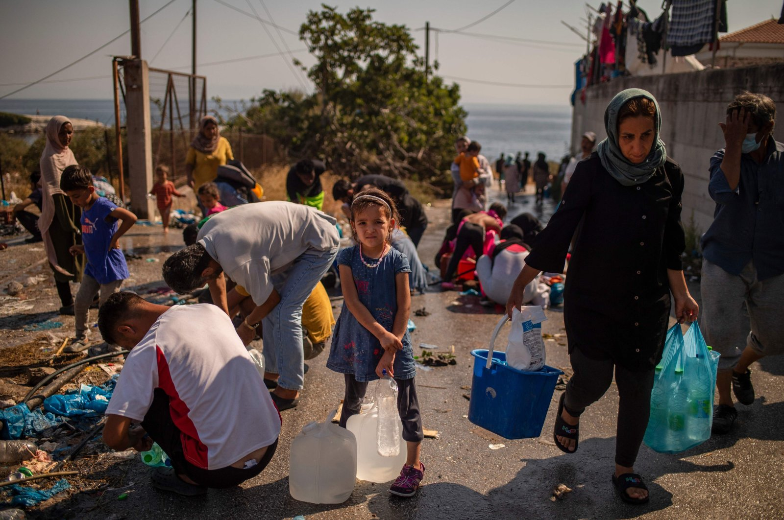 A girl waits to fill bottles with water near a temporary migrant camp on the Greek Aegean island of Lesbos, Sept. 16, 2020. (AFP Photo)