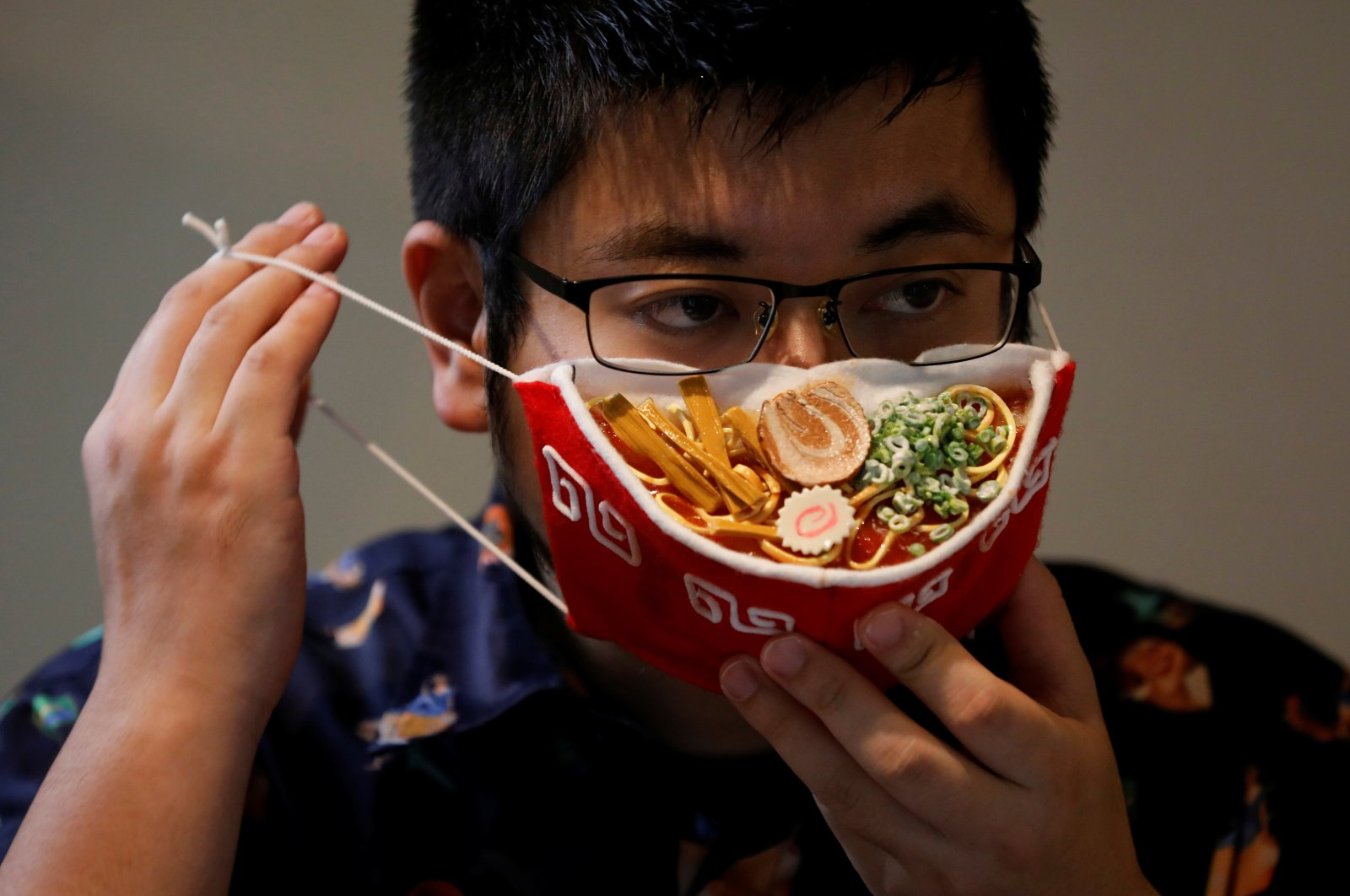 Japanese designer Takahiro Shibata's puts on his protective mask that looks like a steaming bowl of ramen noodle soup at his house, following the coronavirus disease (COVID-19) outbreak in Yokohama, Japan on Sept. 23, 2020. (Reuters Photo)