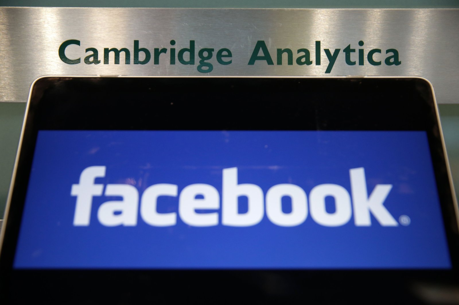 In this file photo, a laptop showing the Facebook logo is held alongside a Cambridge Analytica sign at the entrance to the building housing the offices of Cambridge Analytica in central London, U.K., March 21, 2018. (AFP Photo)