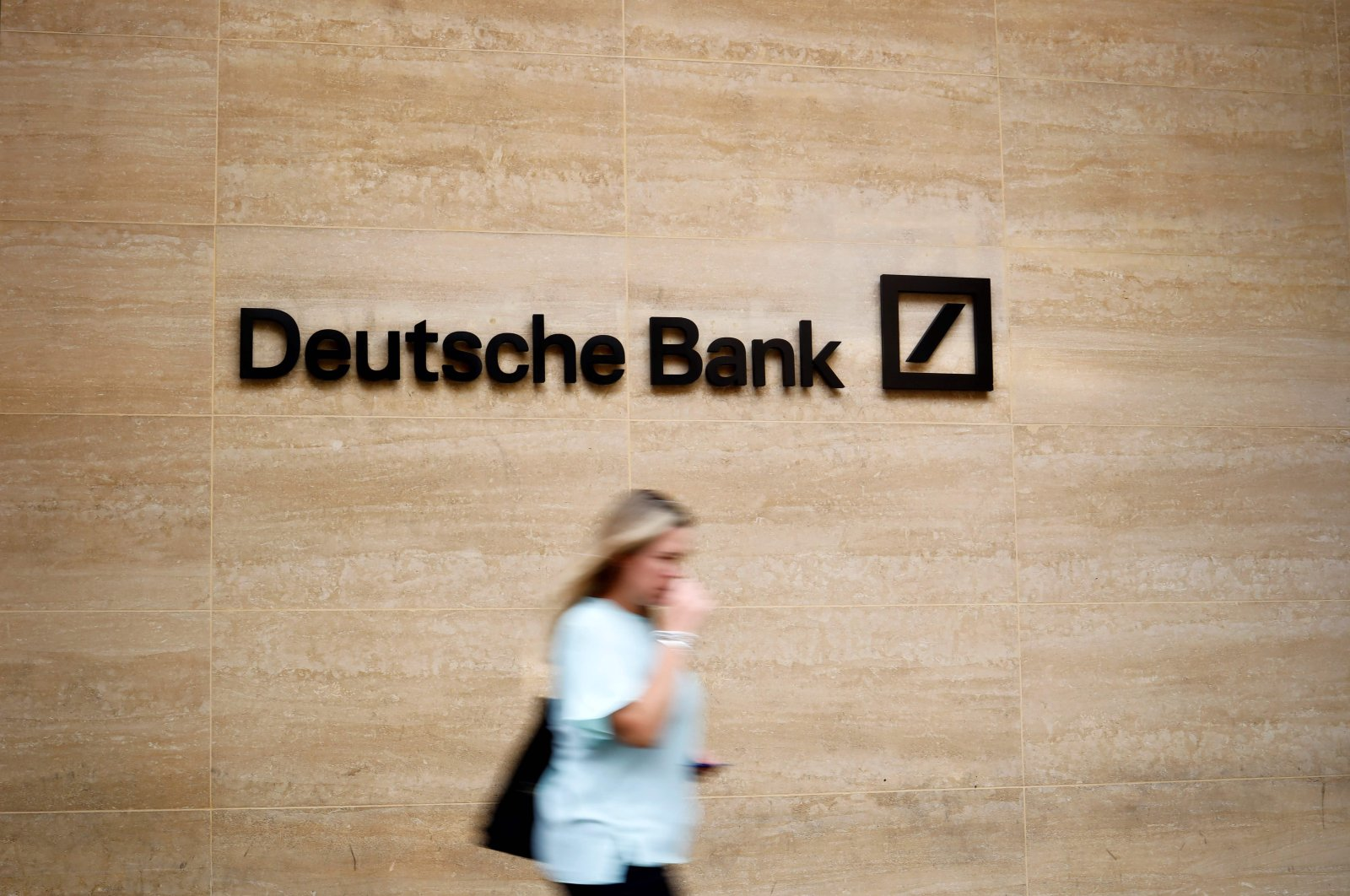 A pedestrian walks past a logo outside the offices of German bank Deutsche Bank in central London, July 08, 2019. (AFP Photo)