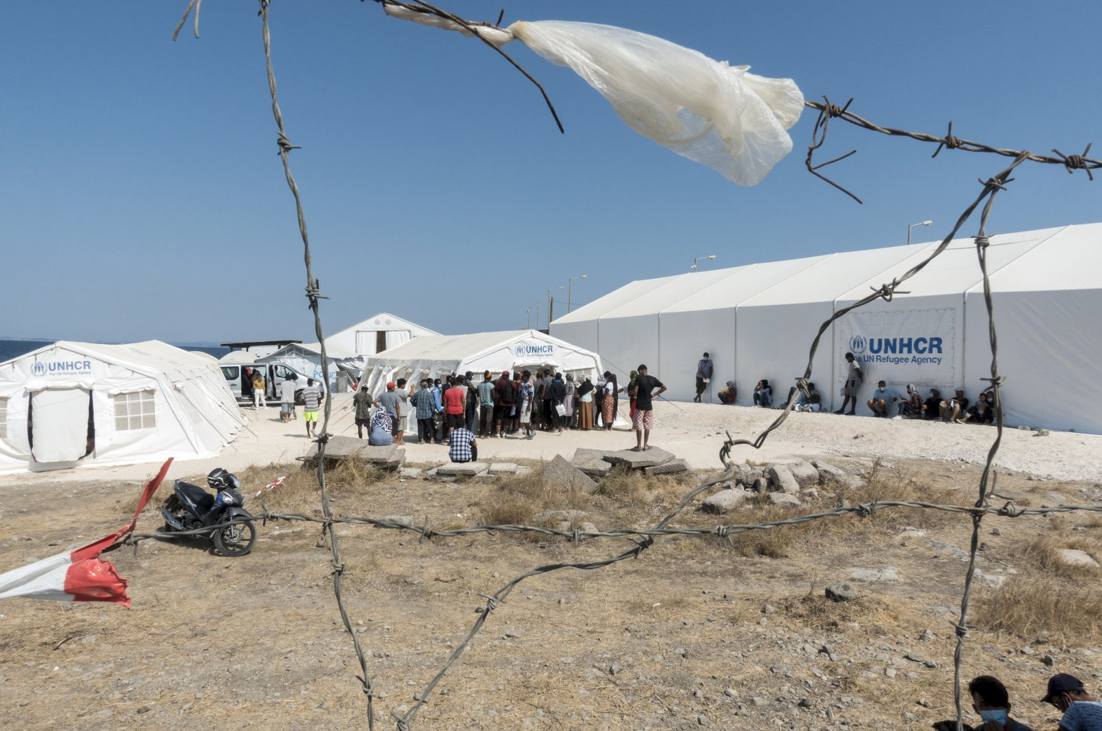 People from the destroyed Moria camp stand outside United Nations High Commissioner for Refugees (UNHCR) tents at a new temporary camp on the island of Lesbos, Greece, Sept. 24, 2020 (AA Photo)