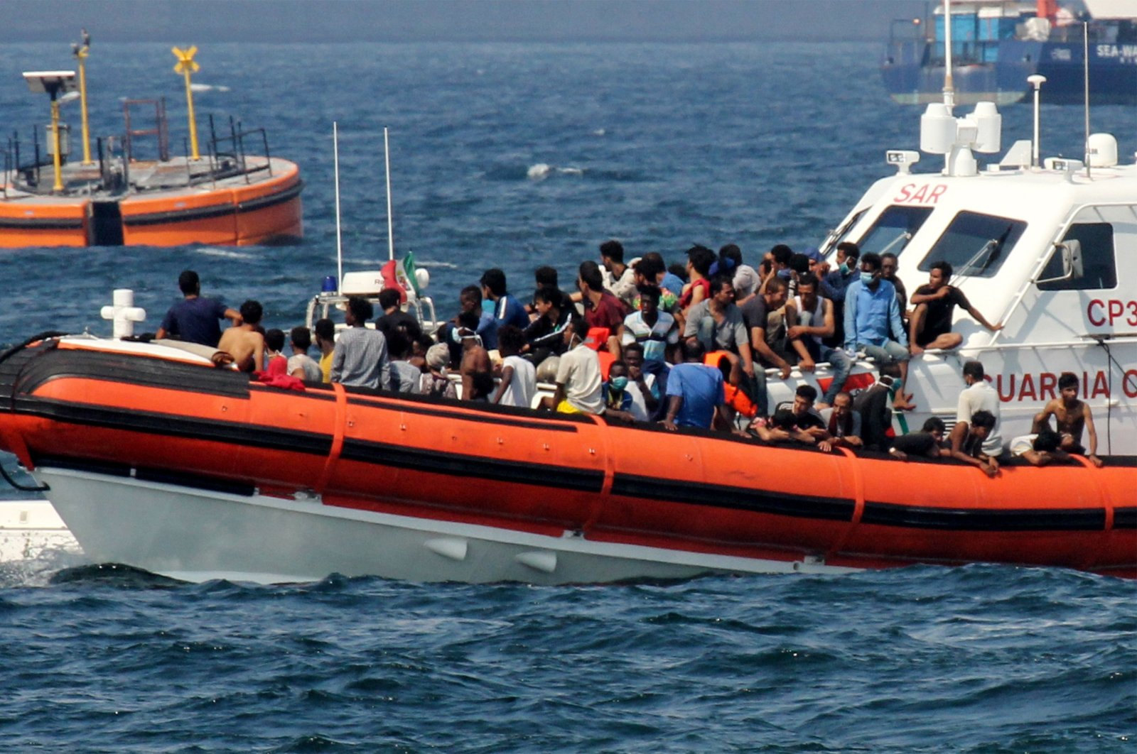 A patrol boat of the Italian Coast Guards (Guardia Costiera) transports migrants towards the port of Palermo, Sicily after they rescued them at sea after a group of 76 migrants threw themselves into the water from the rescue vessel of Spanish non-governmental organization Open Arms, off Palermo, Sicily, Italy, Sept. 17, 2020. (AFP Photo)