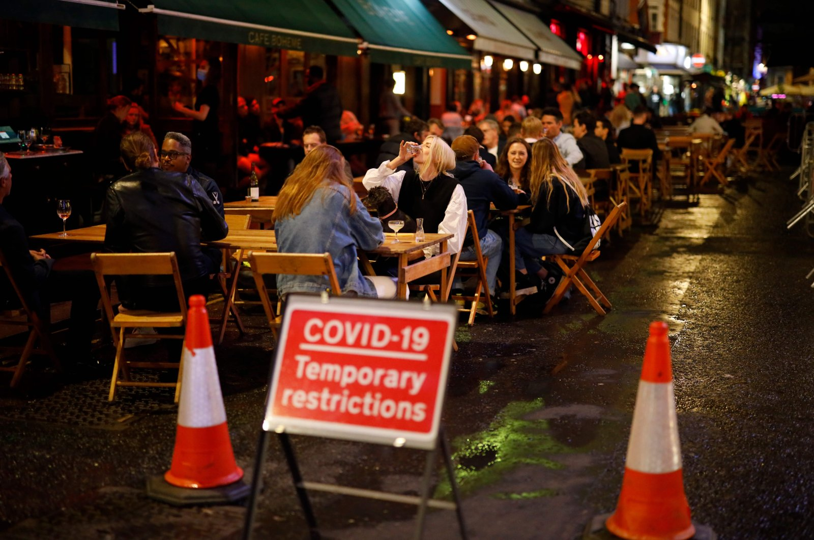 People drink at the outside tables of a cafe in Soho, in central London, Britain, Sept. 23, 2020 (AFP Photo)